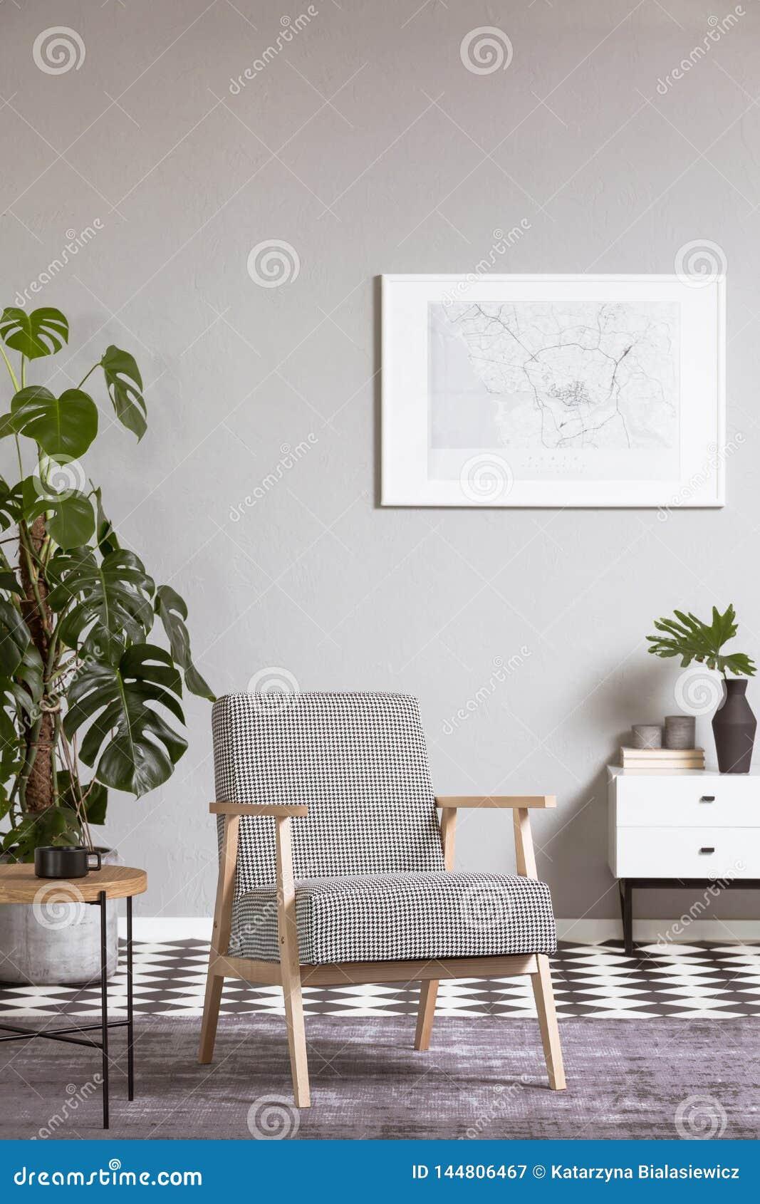 Κομψή εκλεκτής ποιότητας πολυθρόνα στο εσωτερικό καθιστικών με τη ζωγραφική στον τοίχο
