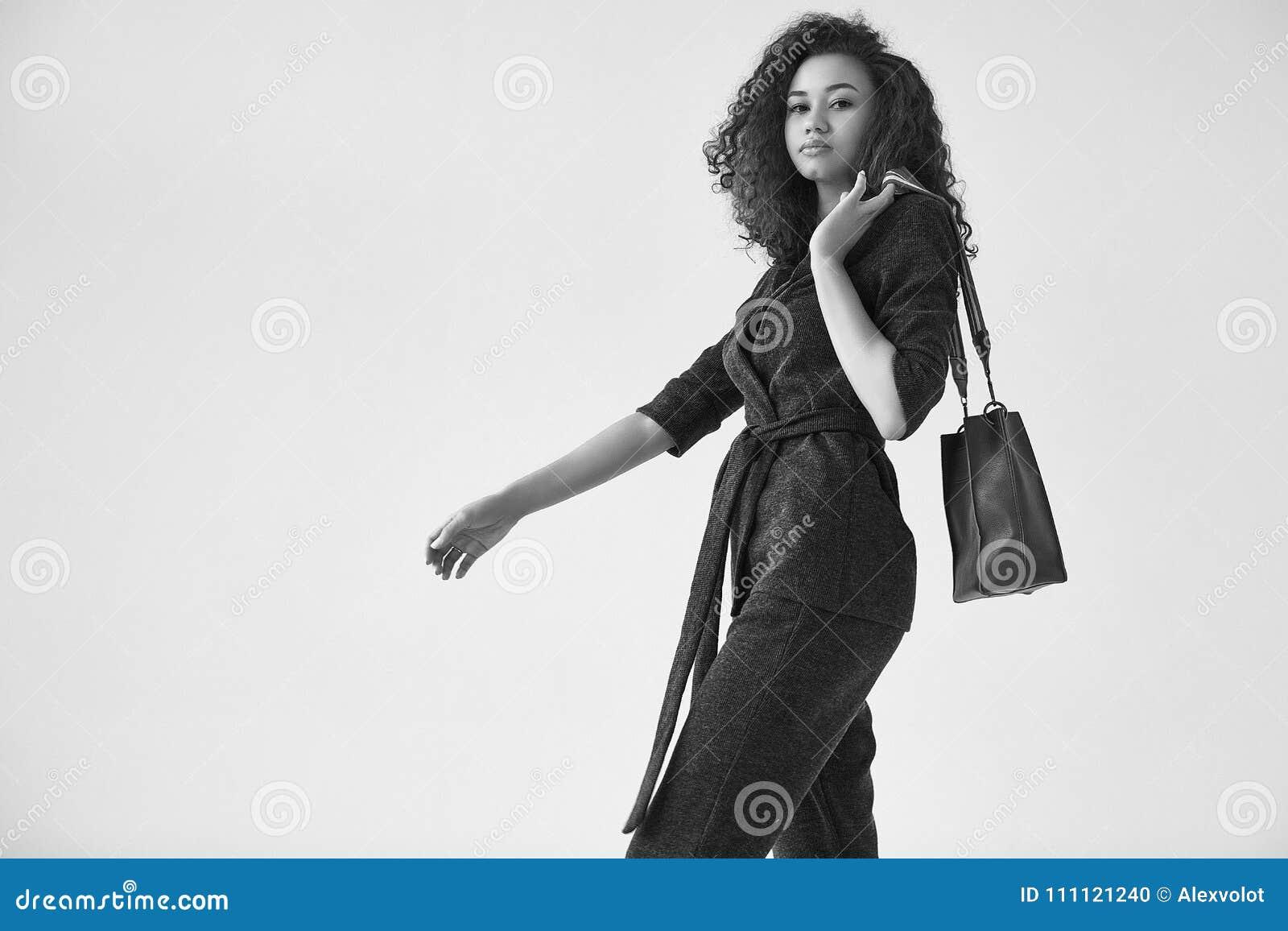 7c3142342cf3 Κομψή μαύρη γυναίκα με τη σγουρή τρίχα στο μοντέρνο πράσινο κοστούμι ...