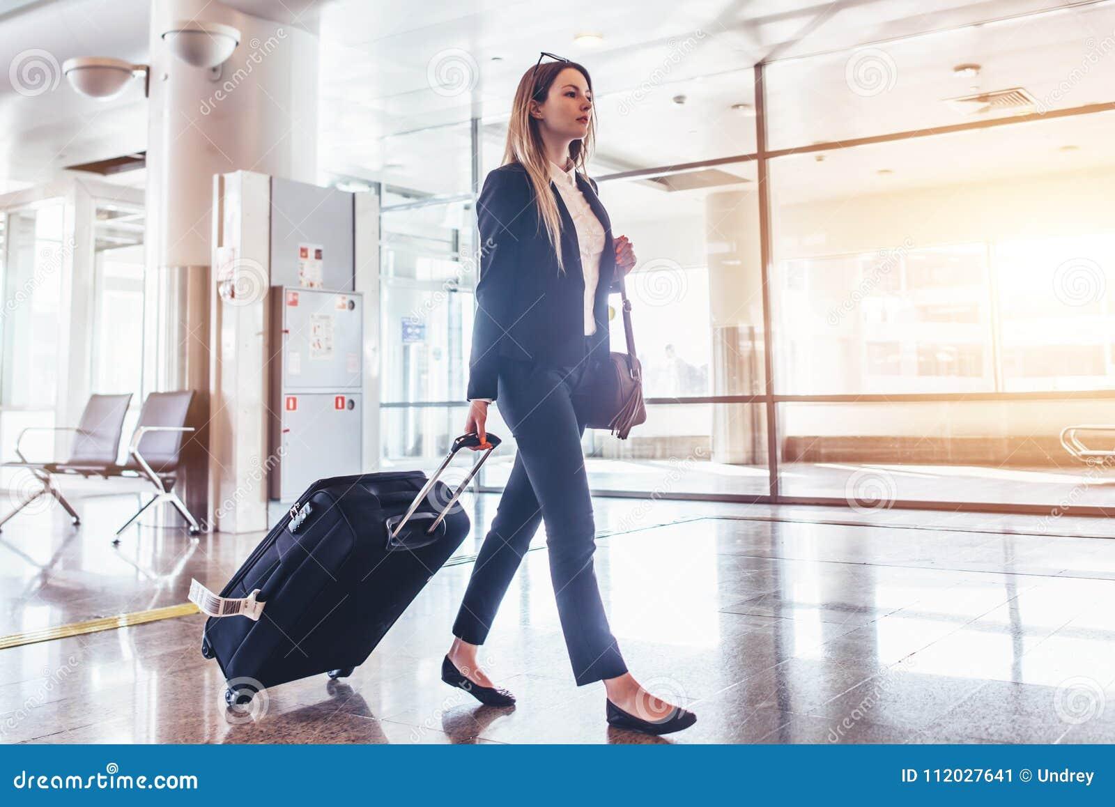 Κομψή νέα γυναίκα που περπατά και που τραβά τη βαλίτσα της στο τερματικό αερολιμένων