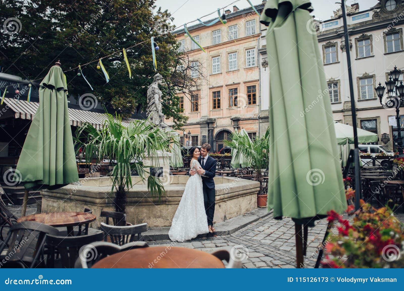 Κομψή νύφη με το νεόνυμφο που περπατά κοντά στον παλαιό καθολικό καθεδρικό ναό