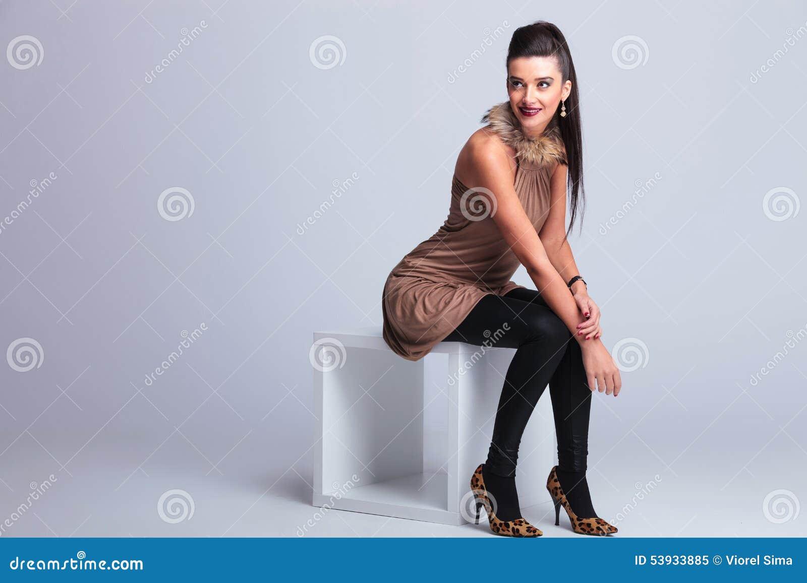 Κομψή συνεδρίαση γυναικών μόδας σε μια καρέκλα χαμογελώντας