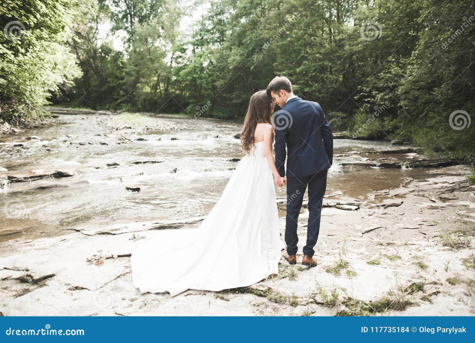 Κομψοί ευγενείς μοντέρνοι νεόνυμφος και νύφη κοντά στον ποταμό με τις πέτρες Γαμήλιο ζεύγος ερωτευμένο