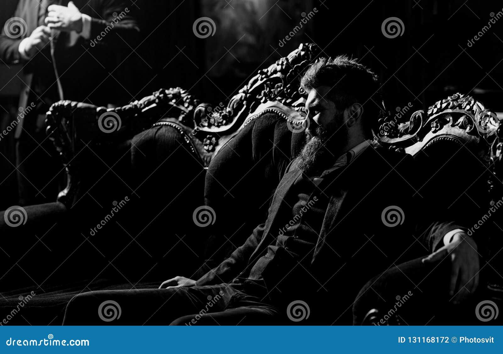 Κομψός νεαρός άνδρας με τη συνεδρίαση γενειάδων σε έναν καναπέ στο εκλεκτής ποιότητας roo