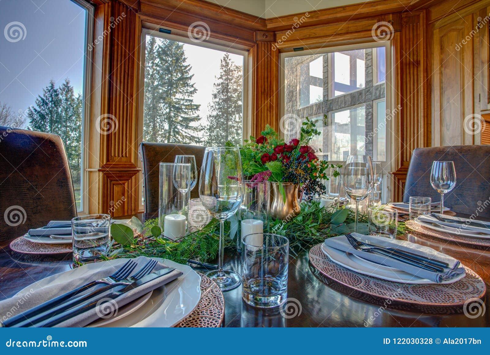 Κομψός πίνακας που τίθεται για το γεύμα και την όμορφη άποψη παραθύρων