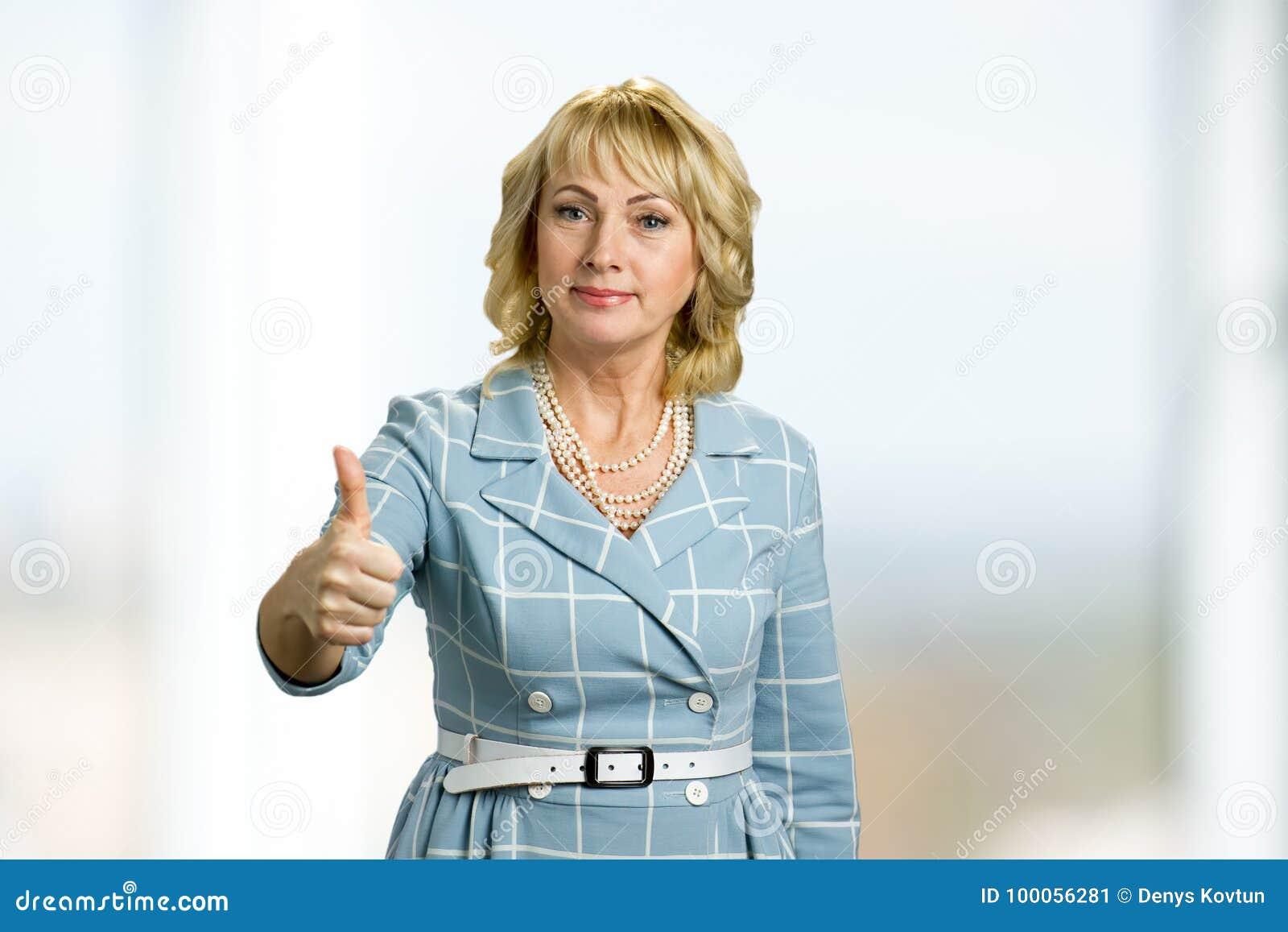 Κομψός ώριμος αυξημένος γυναίκα αντίχειρας επάνω