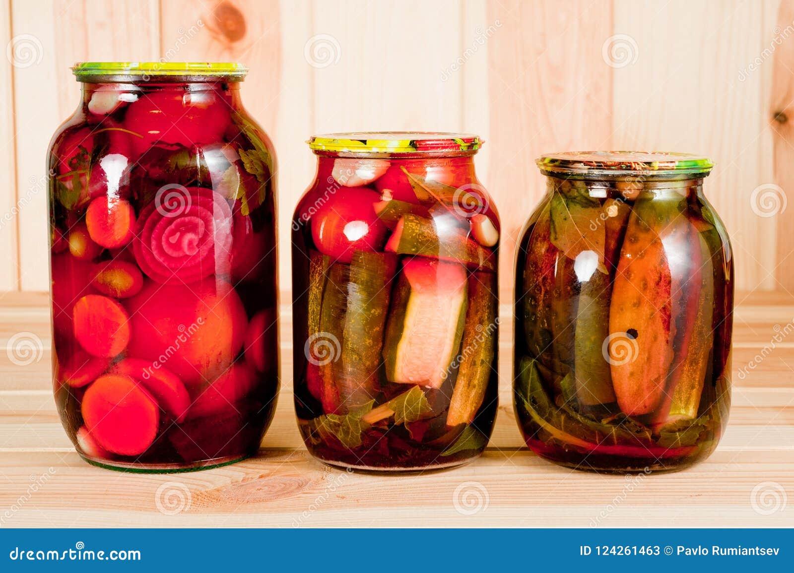 Κονσερβοποιημένα ντομάτες και αγγούρια σε ένα βάζο γυαλιού σε ένα ξύλινο υπόβαθρο
