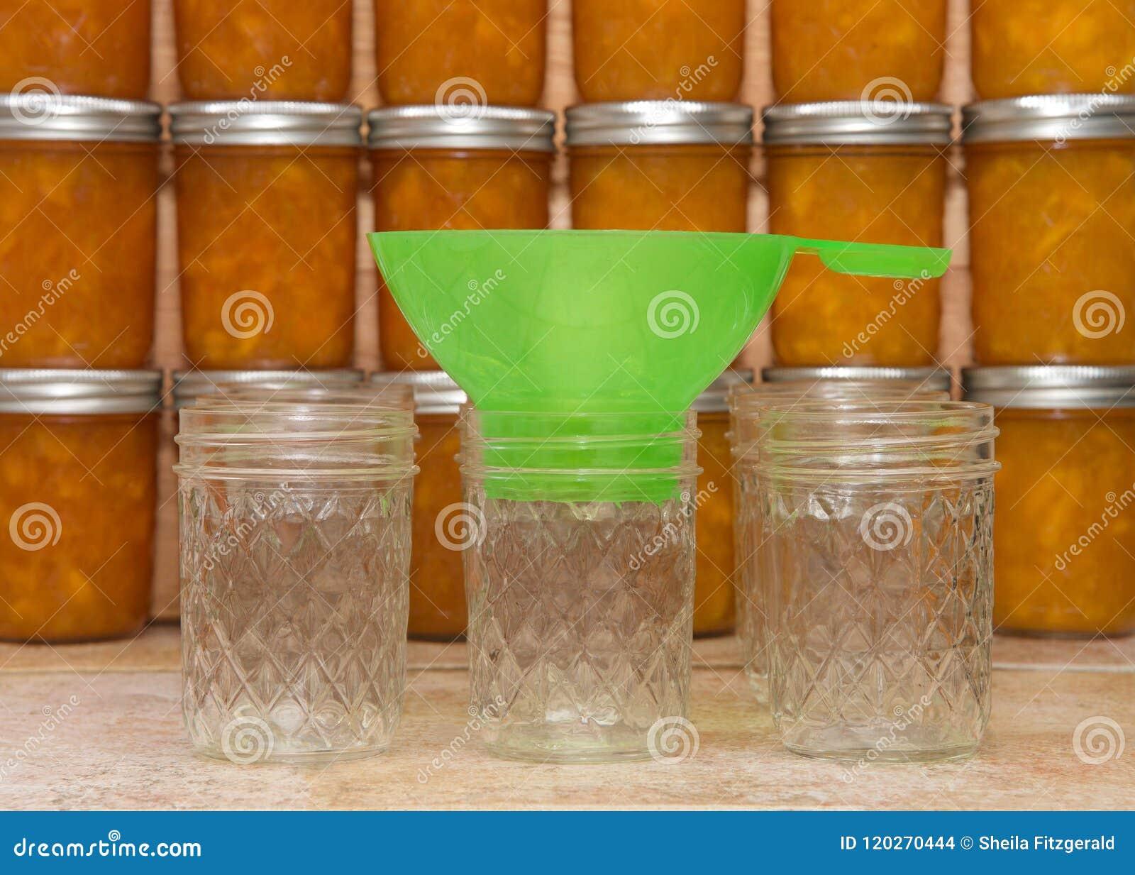 Κονσερβοποιώντας προμήθειες μαρμελάδας ροδάκινων στο μετρητή με τα τελειωμένα βάζα στο υπόβαθρο