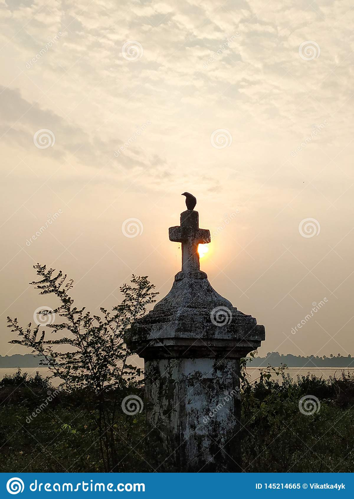 Κοράκι και σταυρός στο ηλιοβασίλεμα
