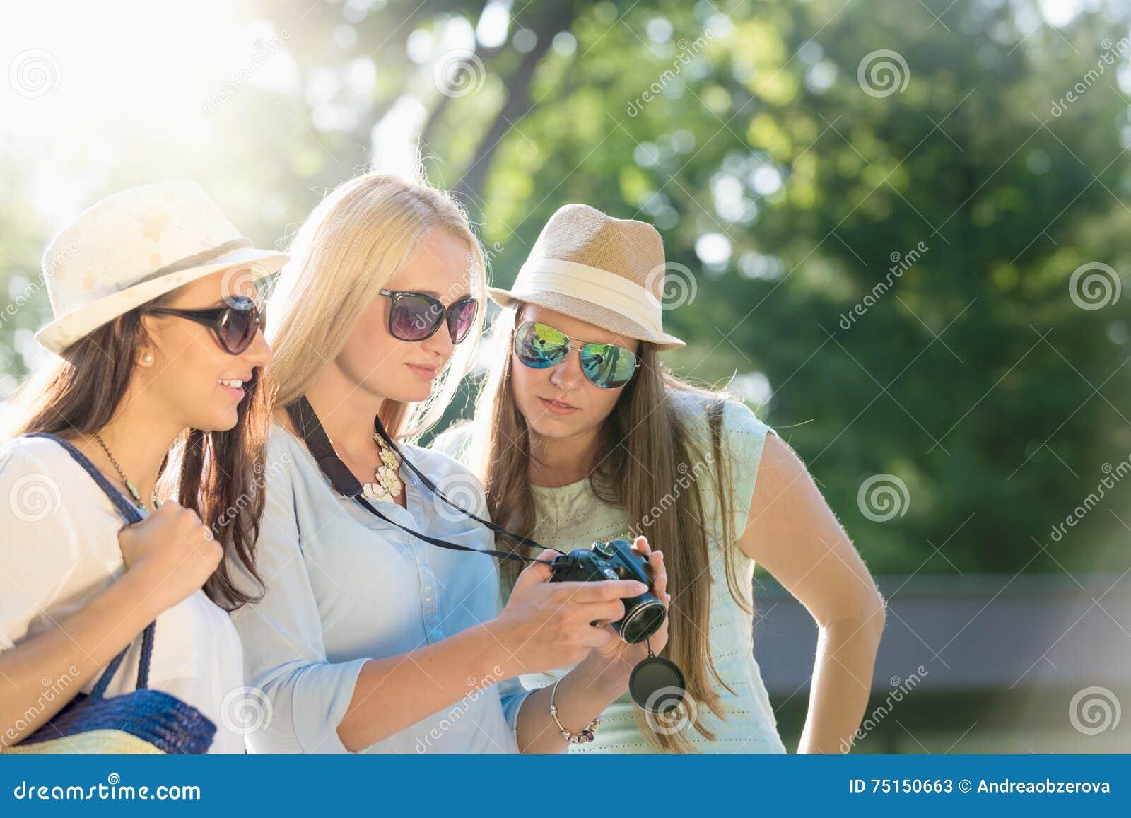 Κορίτσια που εξετάζουν τις φωτογραφίες στη κάμερα τους στις καλοκαιρινές διακοπές