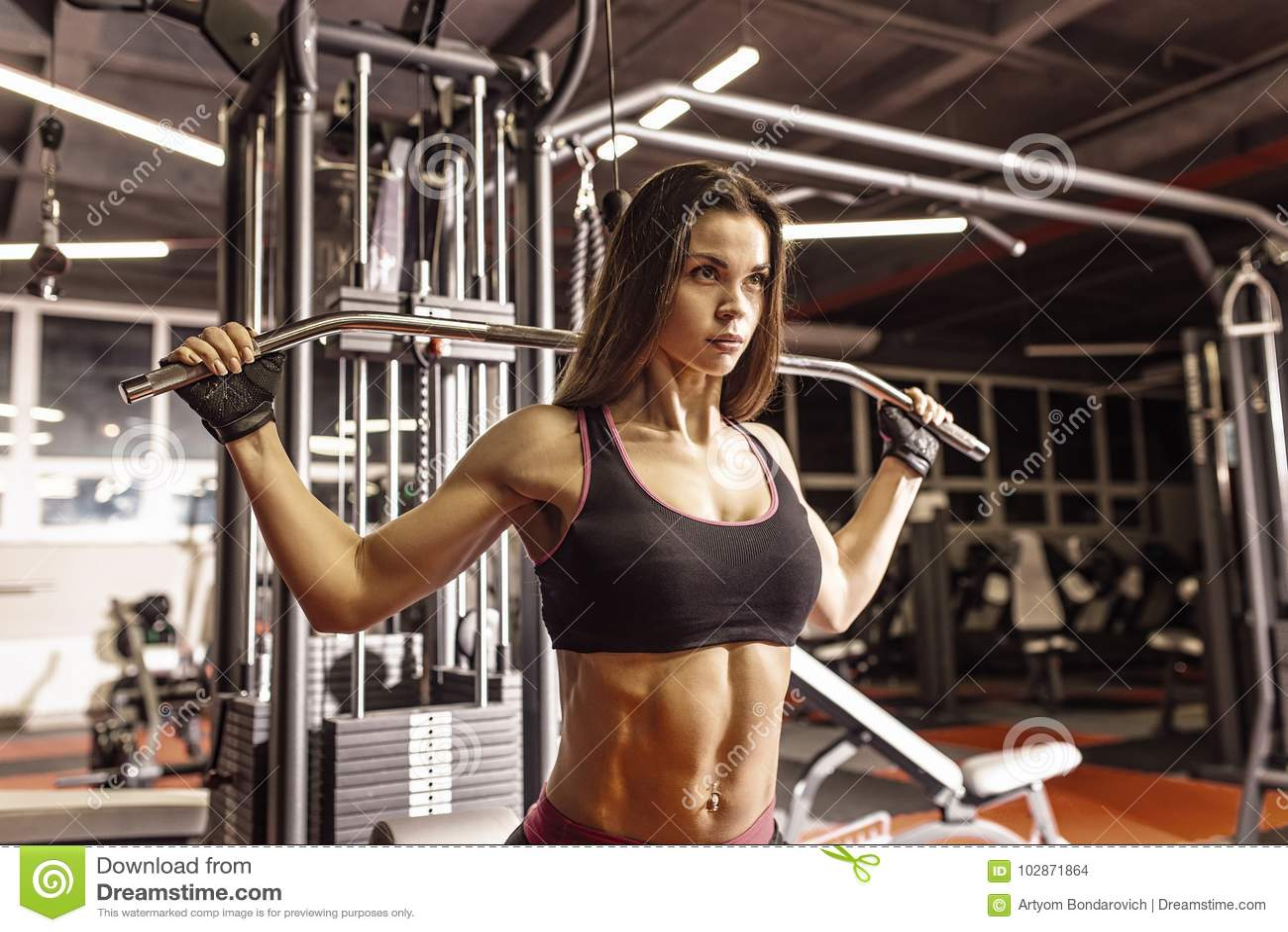 Κορίτσι αθλητών sportswear που επιλύει και που εκπαιδεύει τα όπλα και τους ώμους της με τη μηχανή άσκησης στη γυμναστική