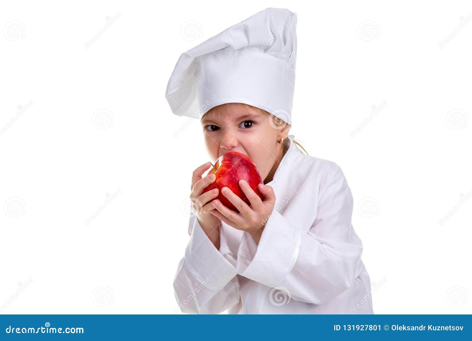 Κορίτσι αρχιμαγείρων σε έναν μάγειρα ΚΑΠ ομοιόμορφο, δαγκώνοντας το κόκκινο μήλο Ανθρώπινες συγκινήσεις, συναίσθημα έκφρασης του