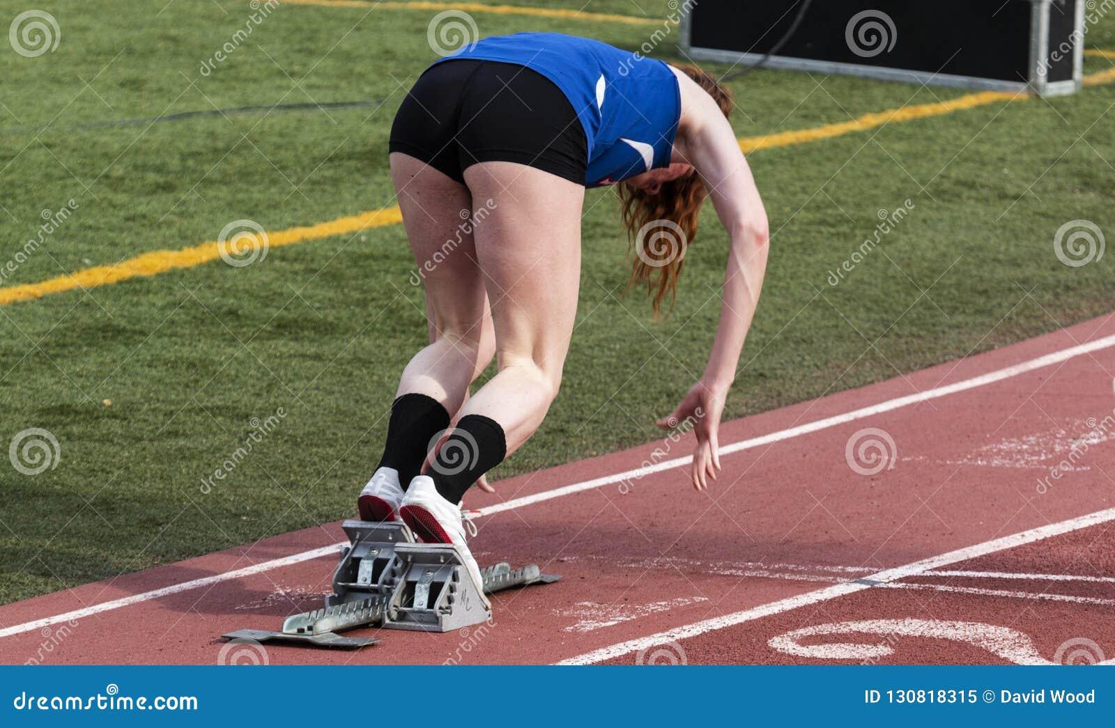 Κορίτσι γυμνασίου sprinter που βγαίνει από τους φραγμούς