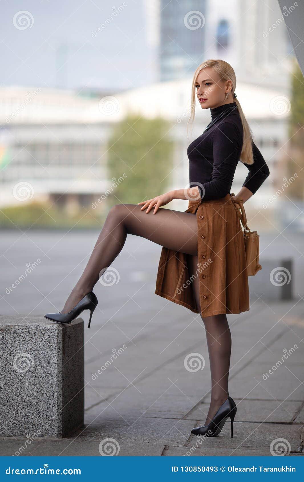 Κορίτσι με τα τέλεια πόδια στο pantyhose στο τετράγωνο πόλεων