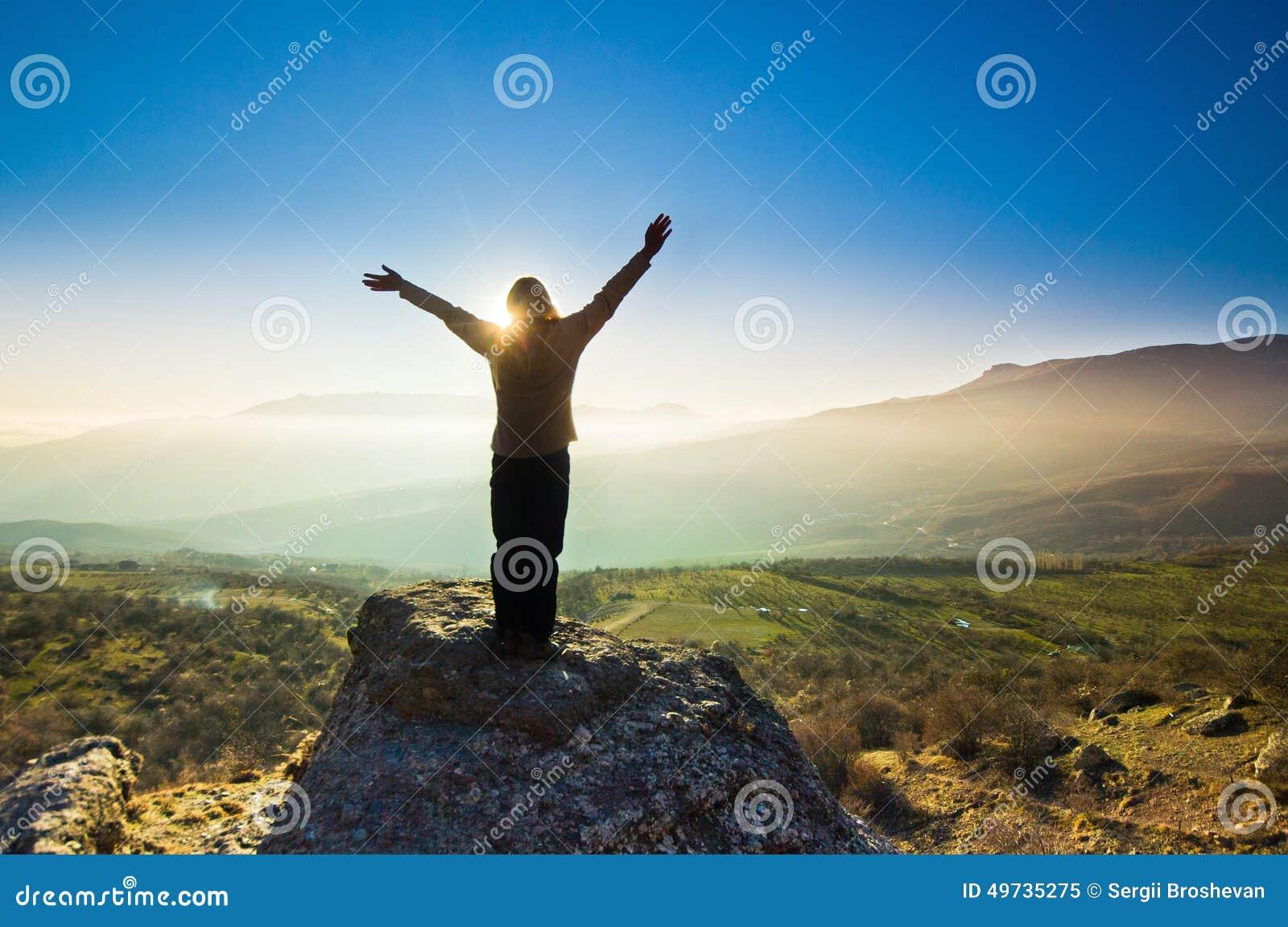 Κορίτσι με τα χέρια επάνω στα βουνά ενάντια στον ήλιο