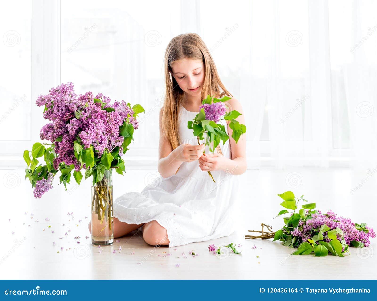 Κορίτσι με την ανθοδέσμη των ιωδών λουλουδιών που κάθεται στο πάτωμα