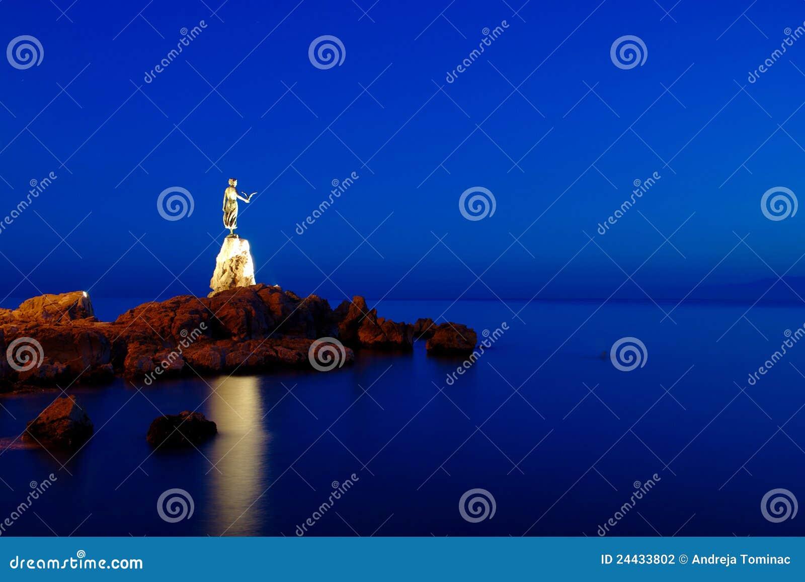 Κορίτσι με seagull κατά τη διάρκεια της μπλε ώρας