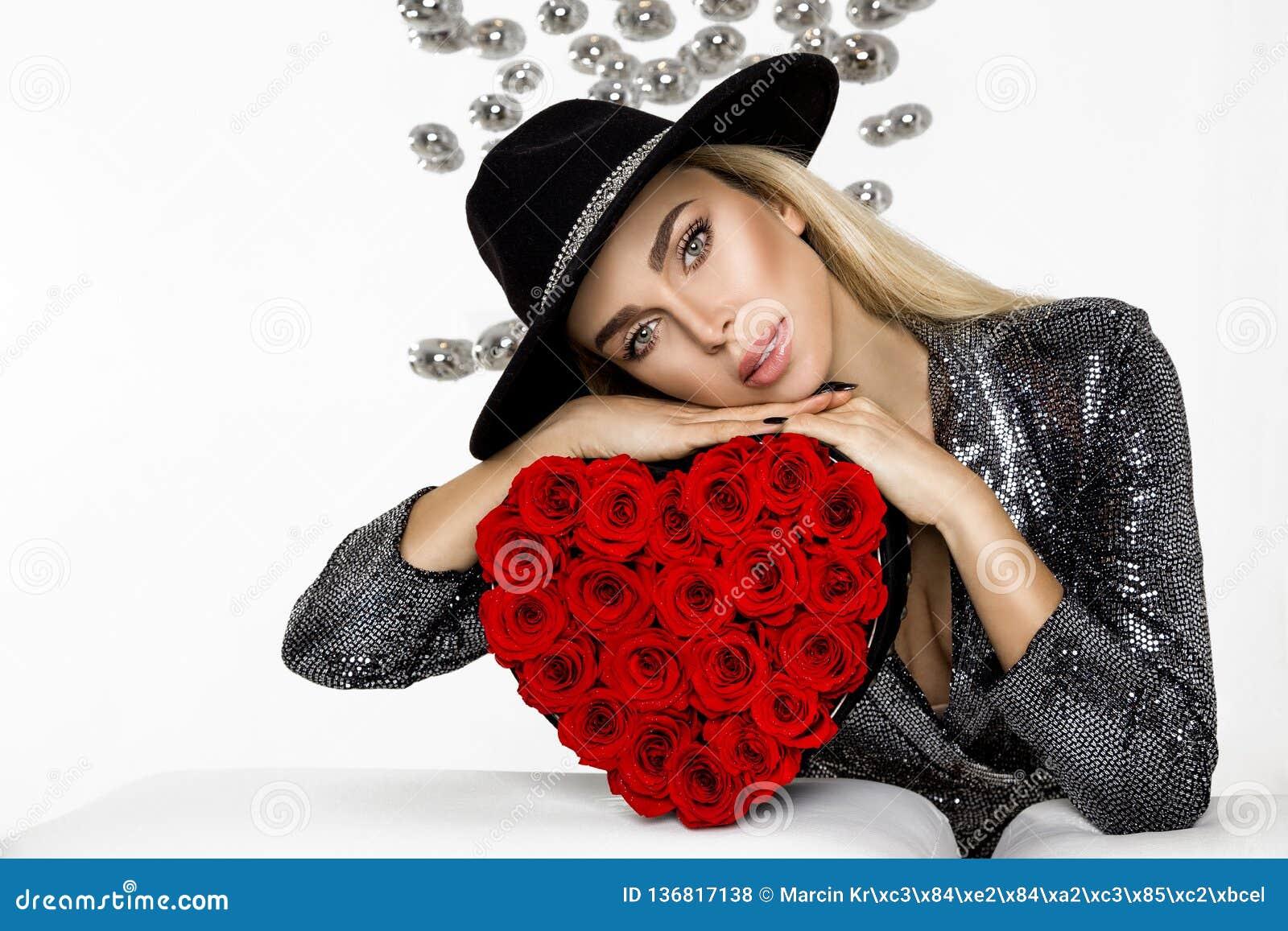 Κορίτσι ομορφιάς βαλεντίνων με τα κόκκινα τριαντάφυλλα καρδιών Πορτρέτο ενός νέου θηλυκού προτύπου με το δώρο και το καπέλο, που