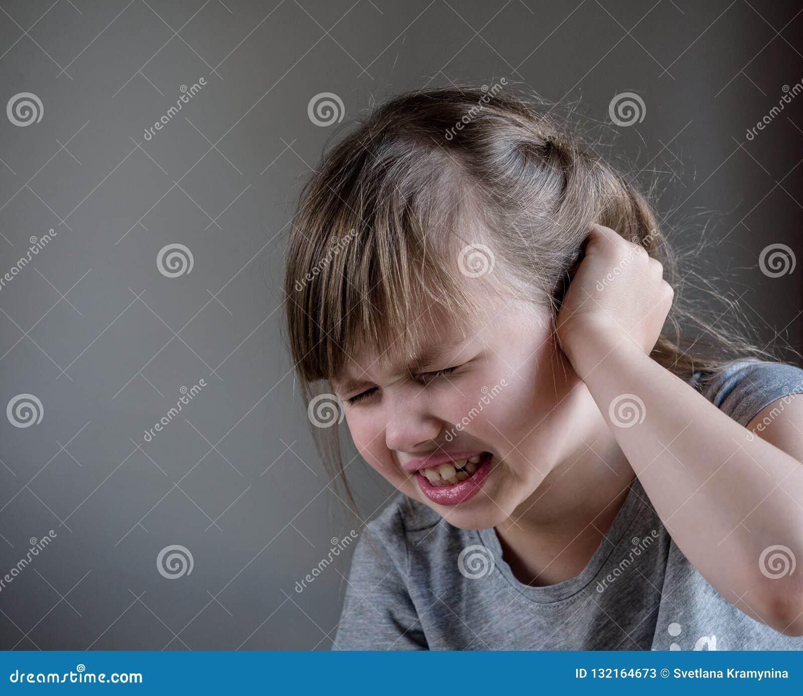 Κορίτσι που έχει τον πόνο αυτιών σχετικά με το επίπονο κεφάλι του απομονωμένο στο γκρίζο υπόβαθρο