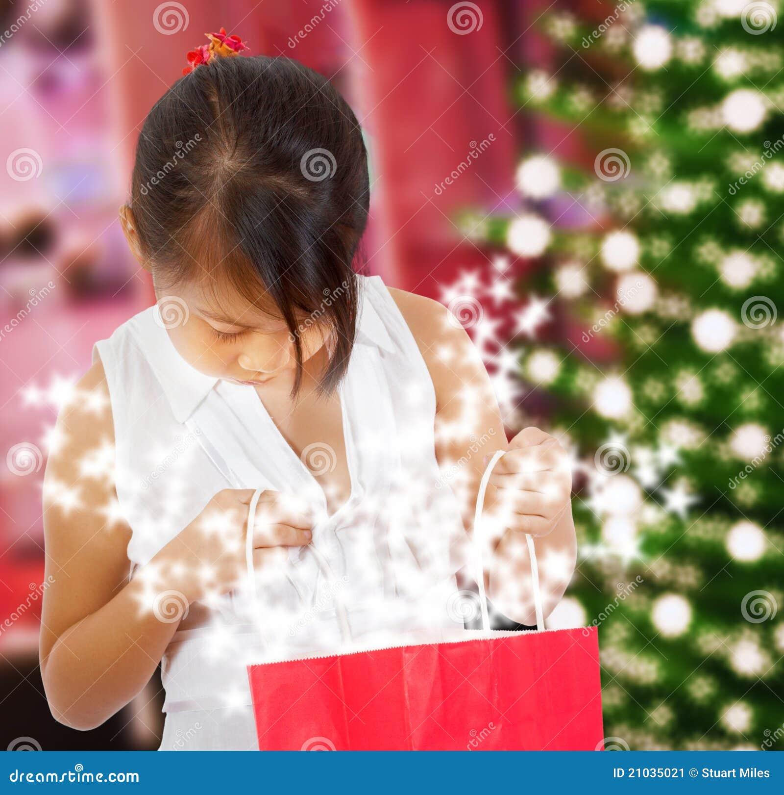 Κορίτσι που εξετάζει το λαμπιρίζοντας δώρο Χριστουγέννων της