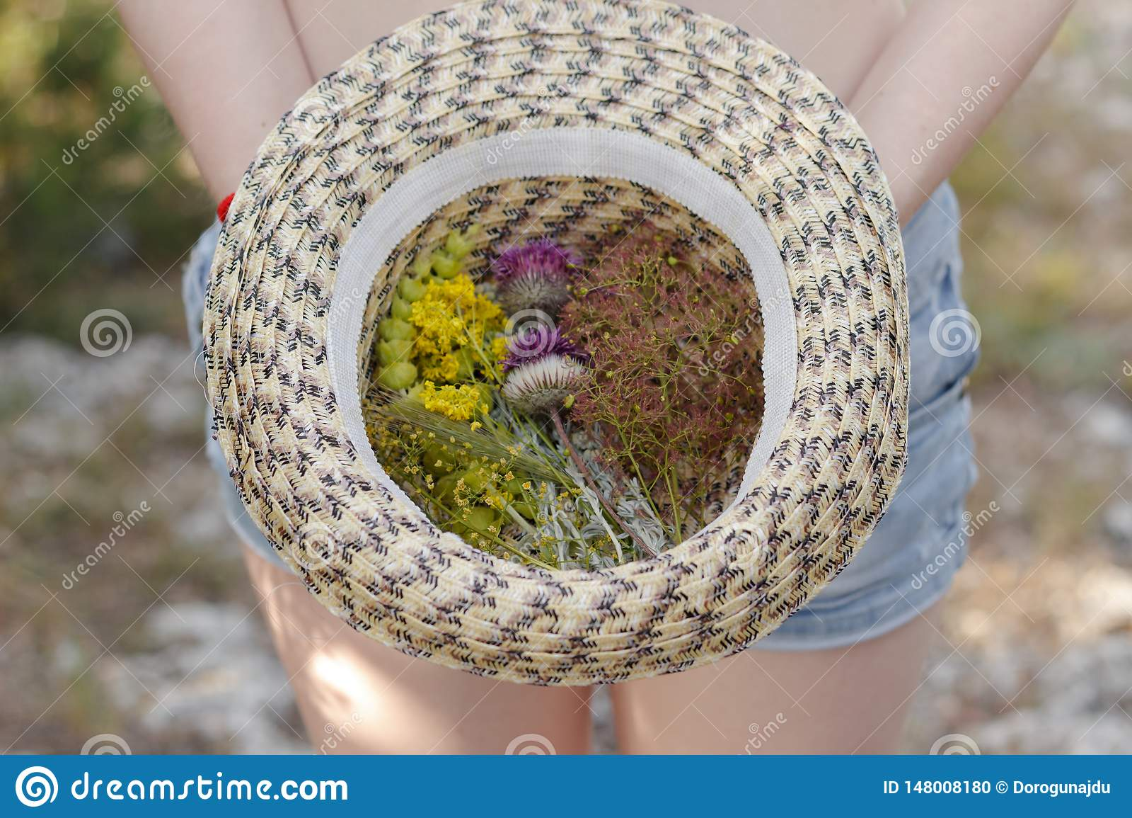 Κορίτσι που κρατά ένα καπέλο αχύρου με μια ανθοδέσμη των όμορφων λουλουδιών