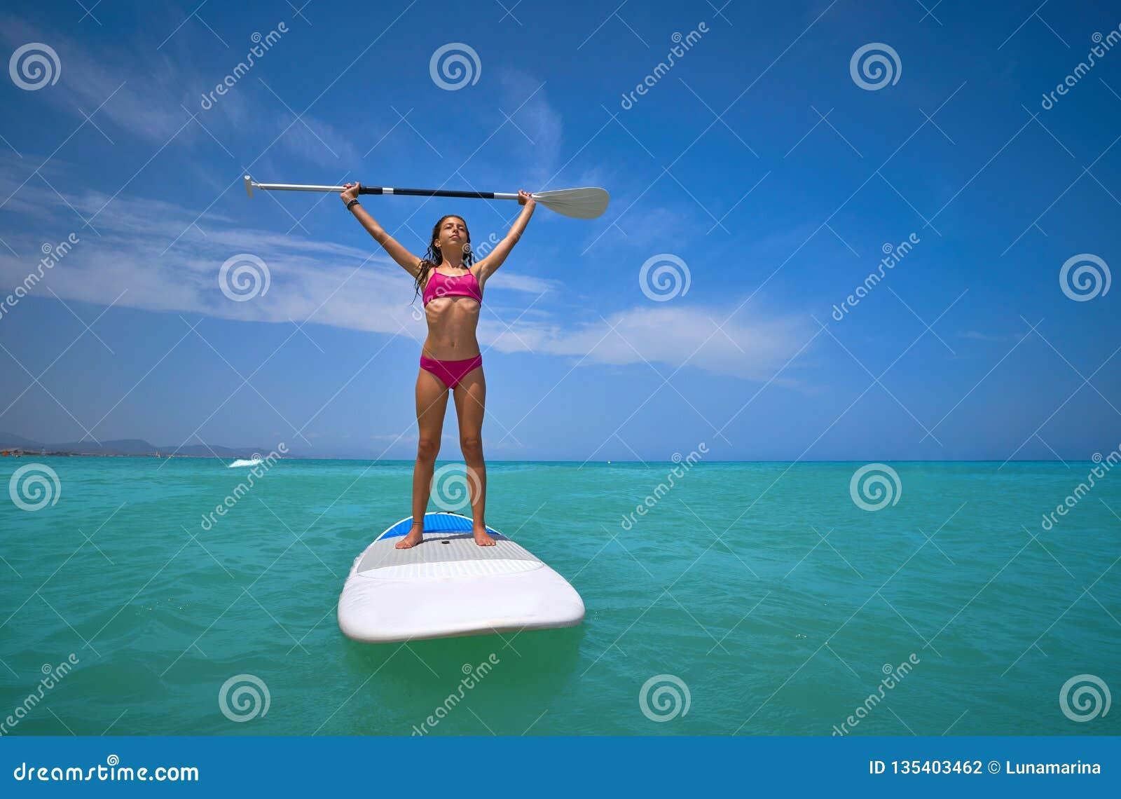 Κορίτσι που στέκεται στη ΓΟΥΛΙΑ πινάκων κυματωγών κουπιών