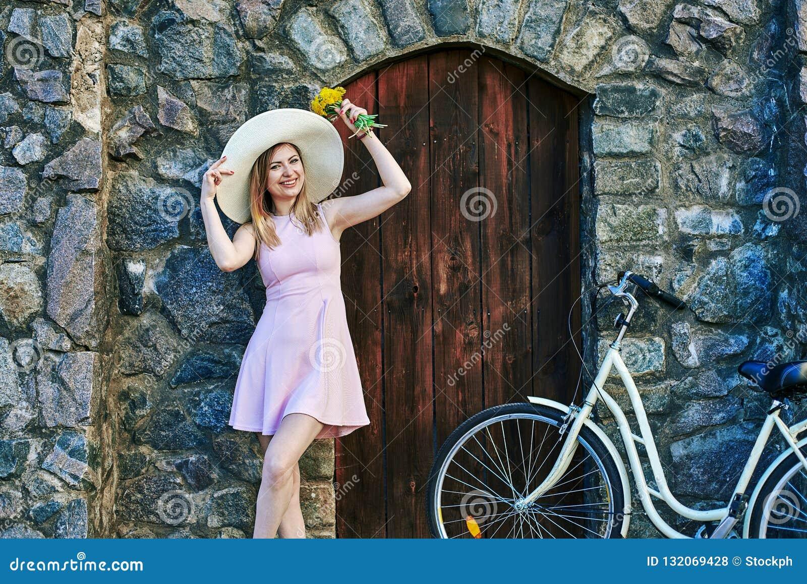 Κορίτσι που χαμογελά στο ρόδινο φόρεμα, καπέλο αχύρου που θέτει το πορτρέτο, που στέκεται κοντά στην κατασκευασμένη πέτρα, τον πα