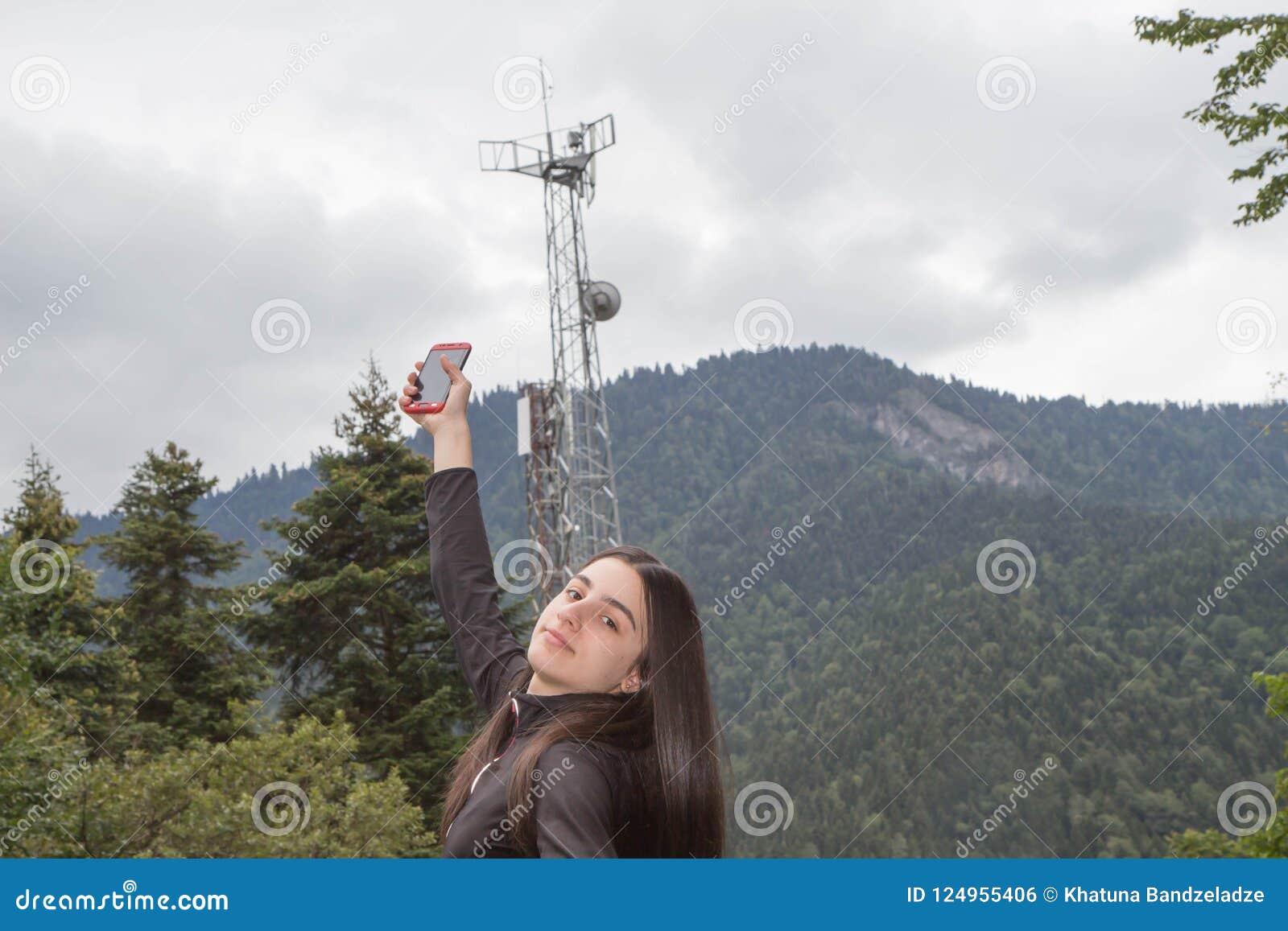 Κορίτσι που χρησιμοποιεί το κινητό τηλέφωνο με τους πύργους τηλεπικοινωνιών με τις κεραίες TV και το δορυφορικό πιάτο