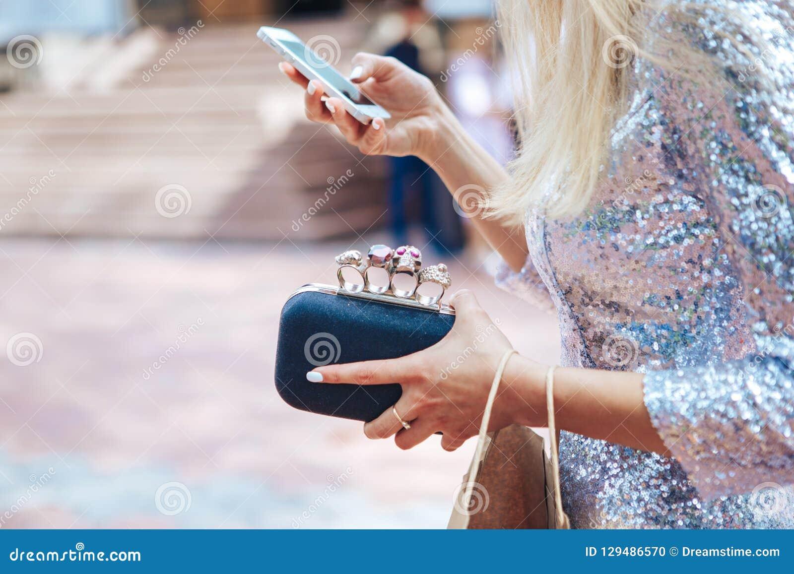 Κορίτσι σε ένα ασημένιο φόρεμα με αρθρώσεις ενός τις μικρές μαύρες τσαντών ορείχαλκου Εξαρτήματα ενδυμάτων μόδας καθορισμένα Αρθρ