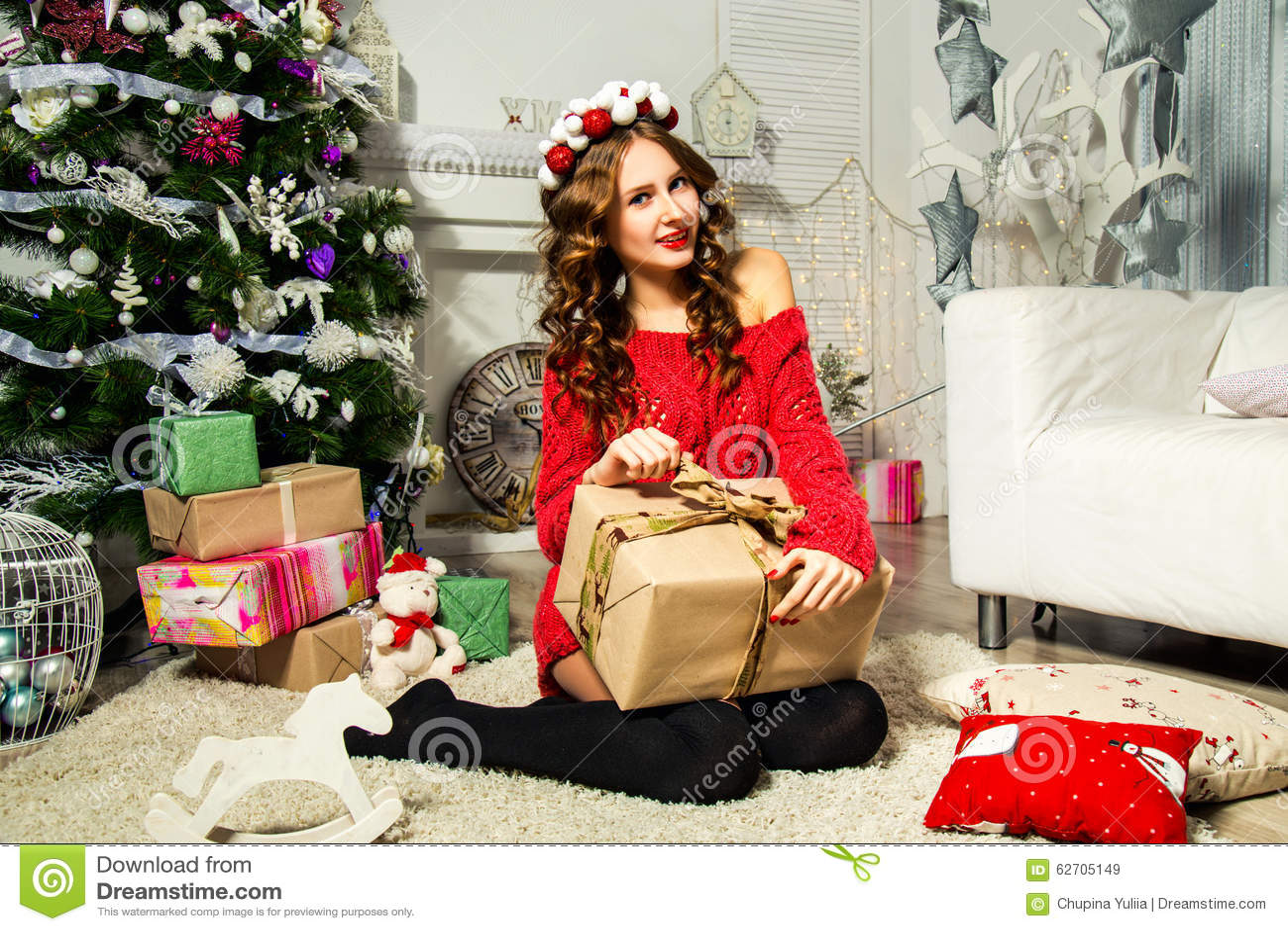 Κορίτσι σε ένα κόκκινο δώρο ανοίγματος πουλόβερ κοντά στο χριστουγεννιάτικο δέντρο Chri
