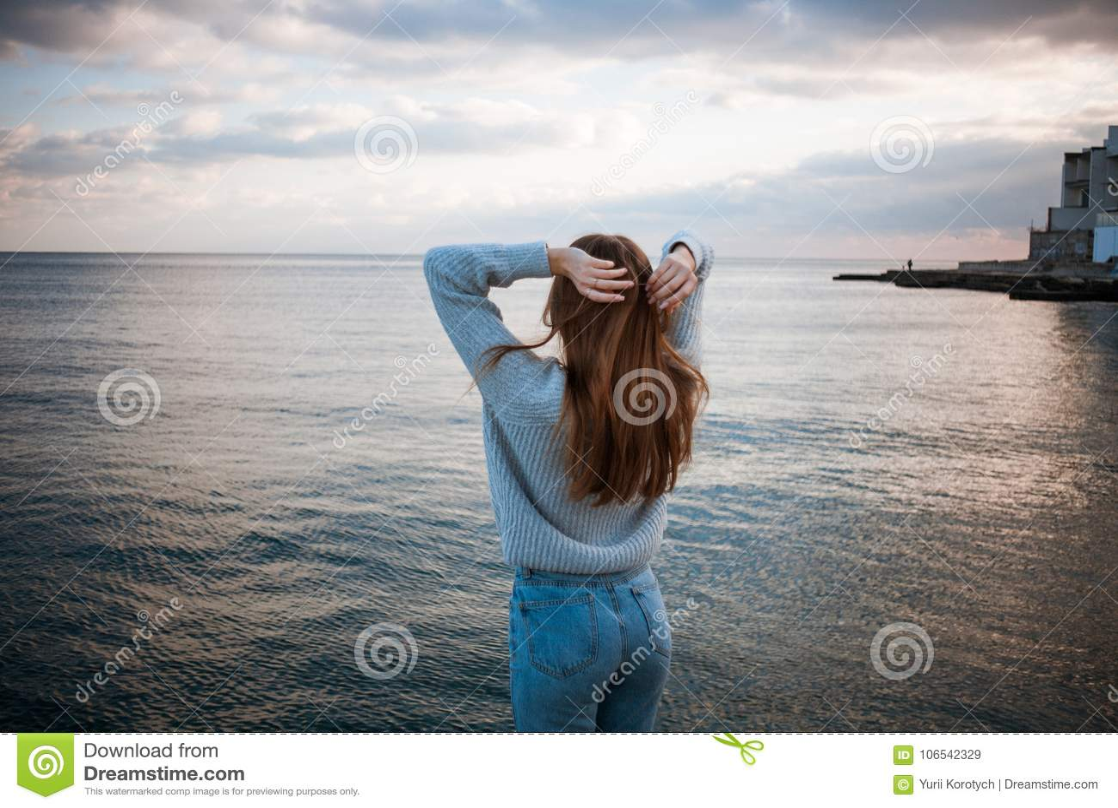 531cdd58834a Το κορίτσι γύρισε μακρυά από τη κάμερα που στέκεται σε ένα πουλόβερ κοντά  στη θάλασσα