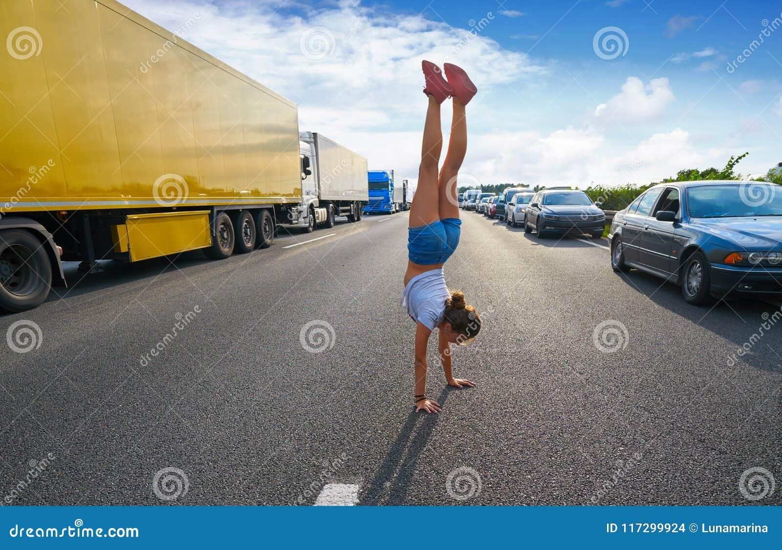 Κορίτσι στάσεων χεριών σε έναν δρόμο κυκλοφοριακής συμφόρησης