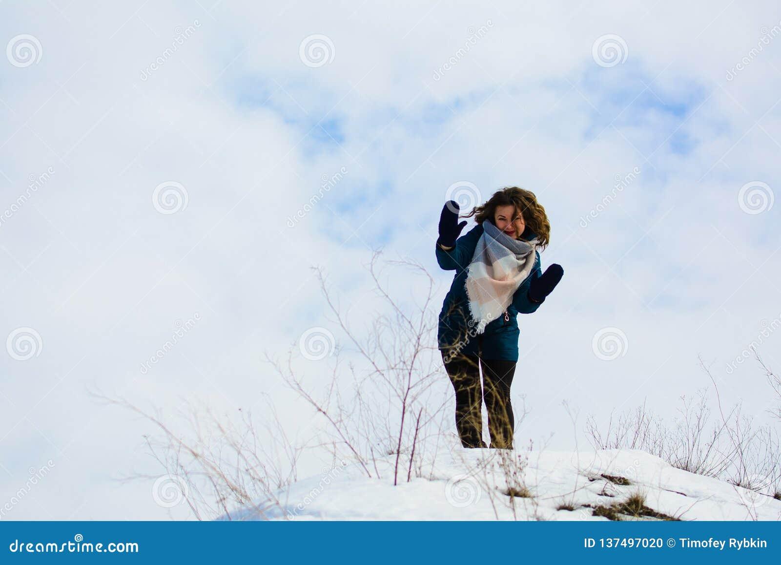 Κορίτσι στις χειμερινές στάσεις σε έναν λόφο με τα χέρια του επάνω έννοια της ελευθερίας ή της νίκης