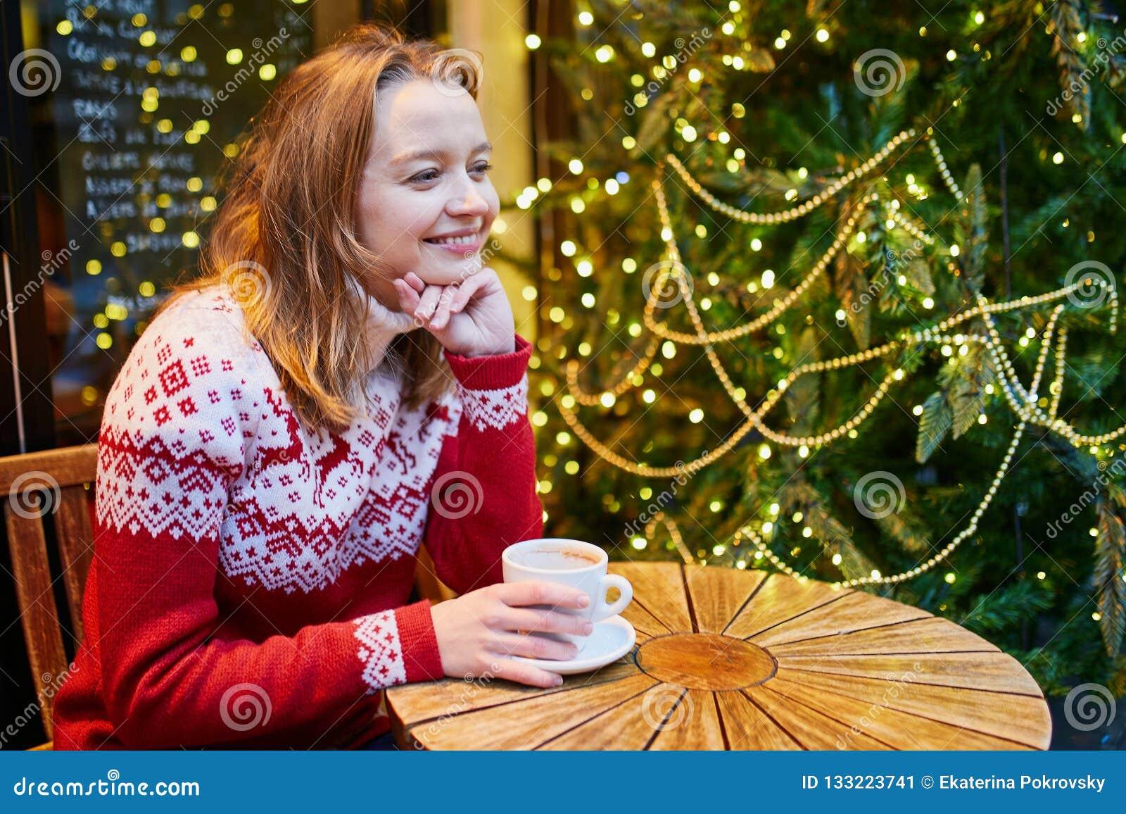 Κορίτσι στον καφέ κατανάλωσης πουλόβερ διακοπών ή καυτή σοκολάτα στον καφέ που διακοσμείται για τα Χριστούγεννα