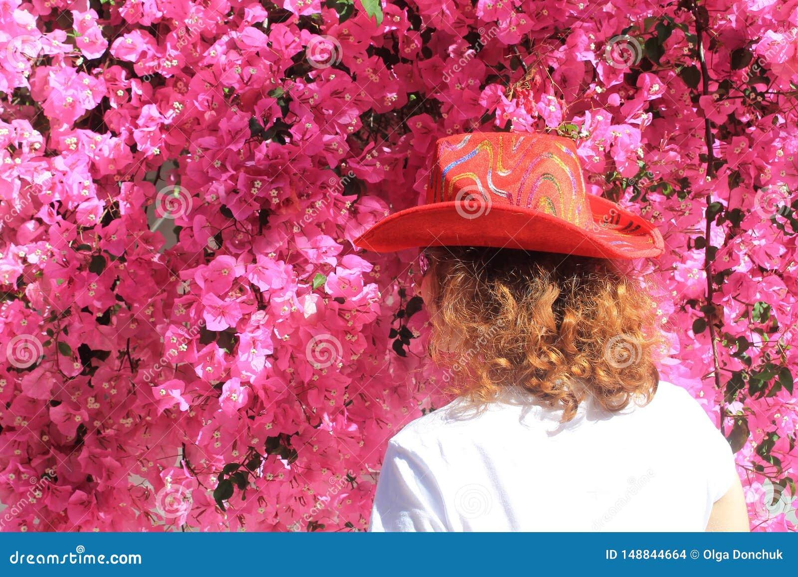 Κορίτσι στο καπέλο του κάουμποϋ μπροστά από τα ρόδινα λουλούδια