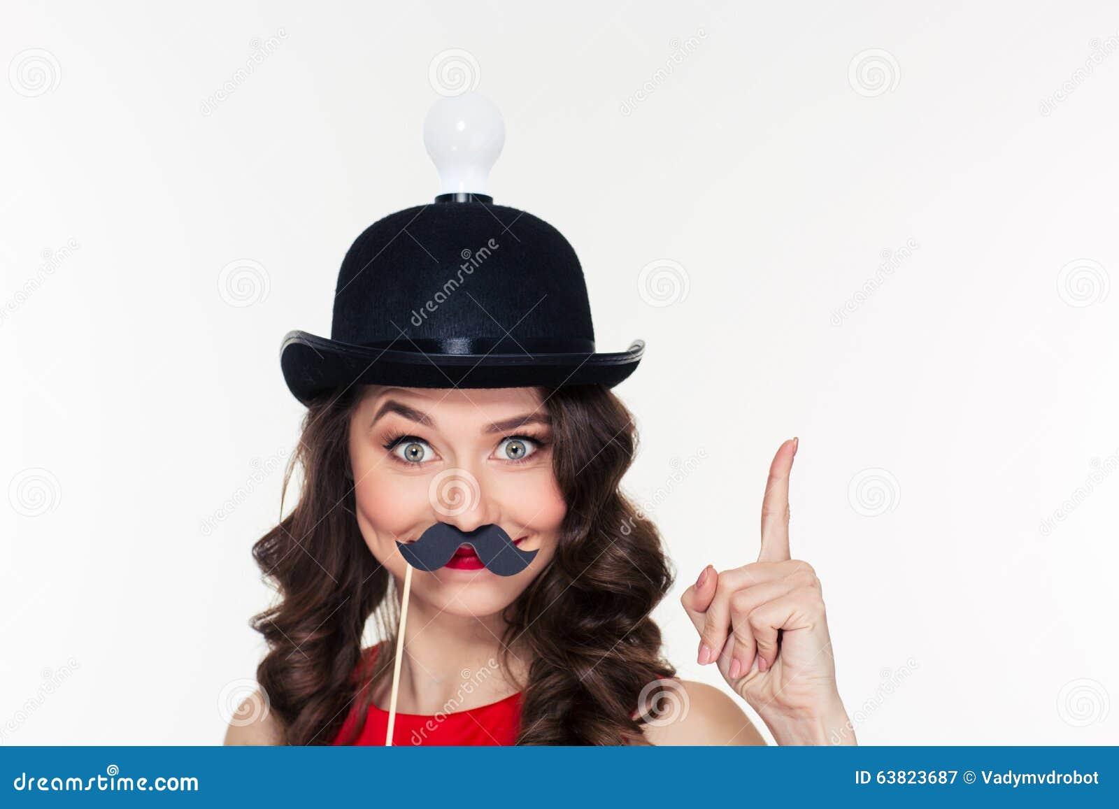 Κορίτσι στο καπέλο με τη λάμπα φωτός που χρησιμοποιεί τα πλαστά στηρίγματα moustache