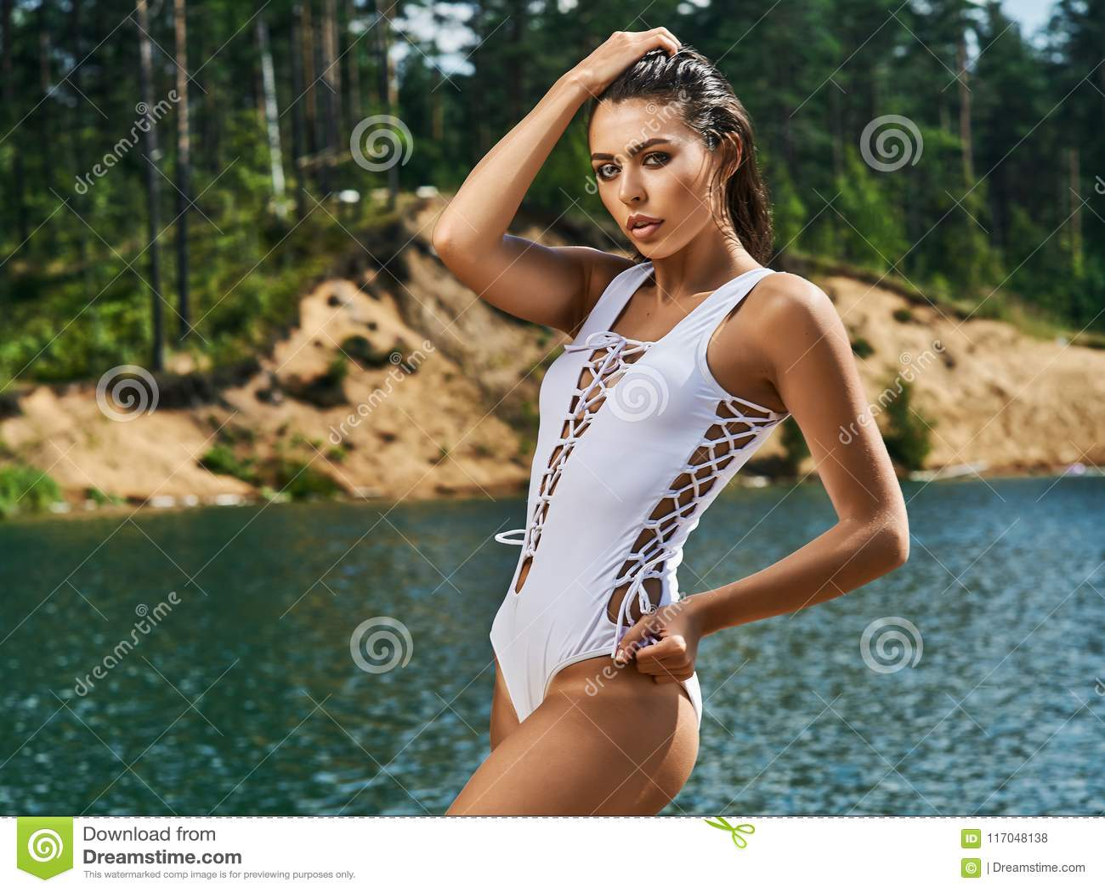 Κορίτσι στο μπικίνι στην παραλία μια ηλιόλουστη ημέρα Θάλασσα και άμμος