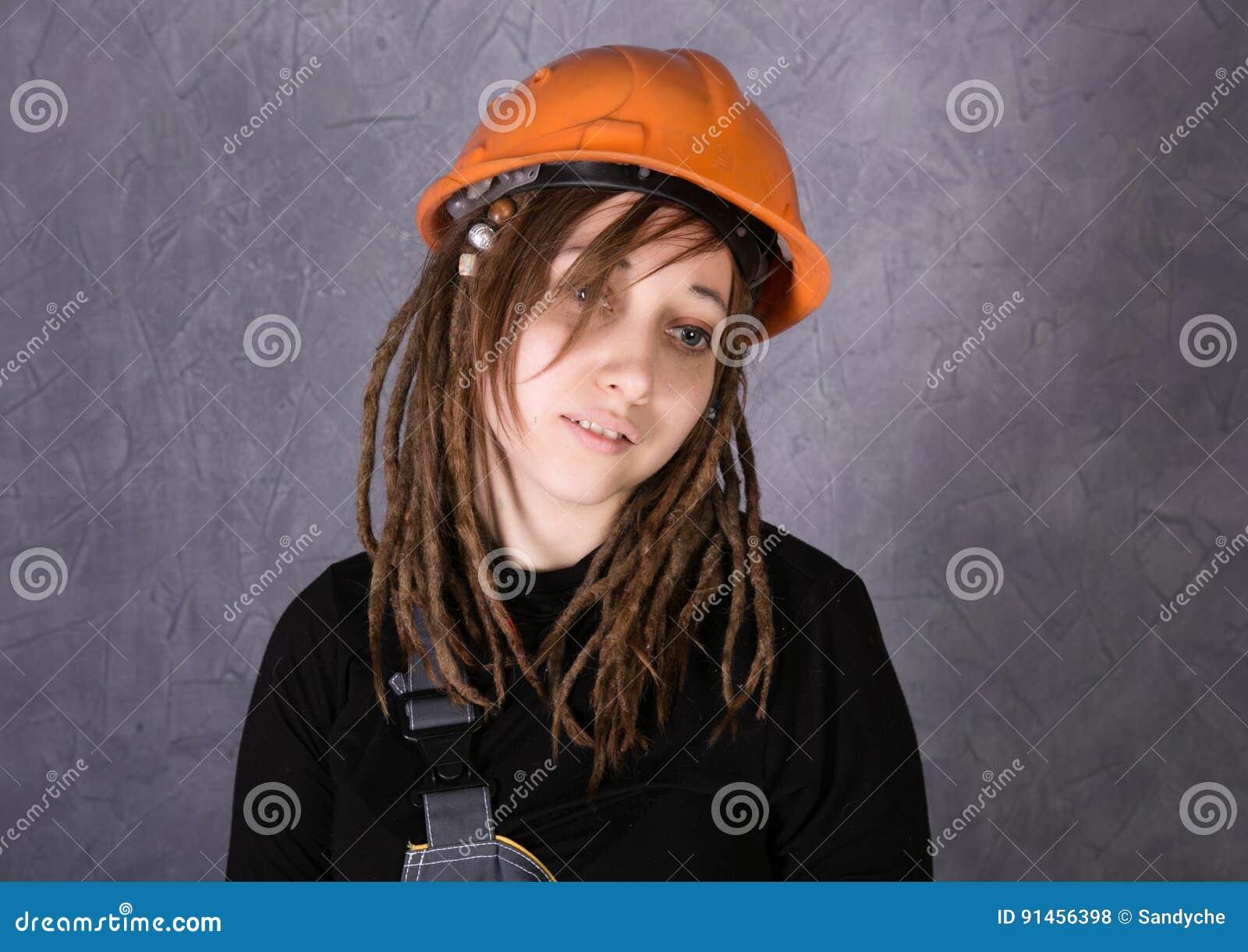 Κορίτσι στο πορτοκαλί εργαλείο σφυριών εκμετάλλευσης φανέλλων κρανών ασφάλειας