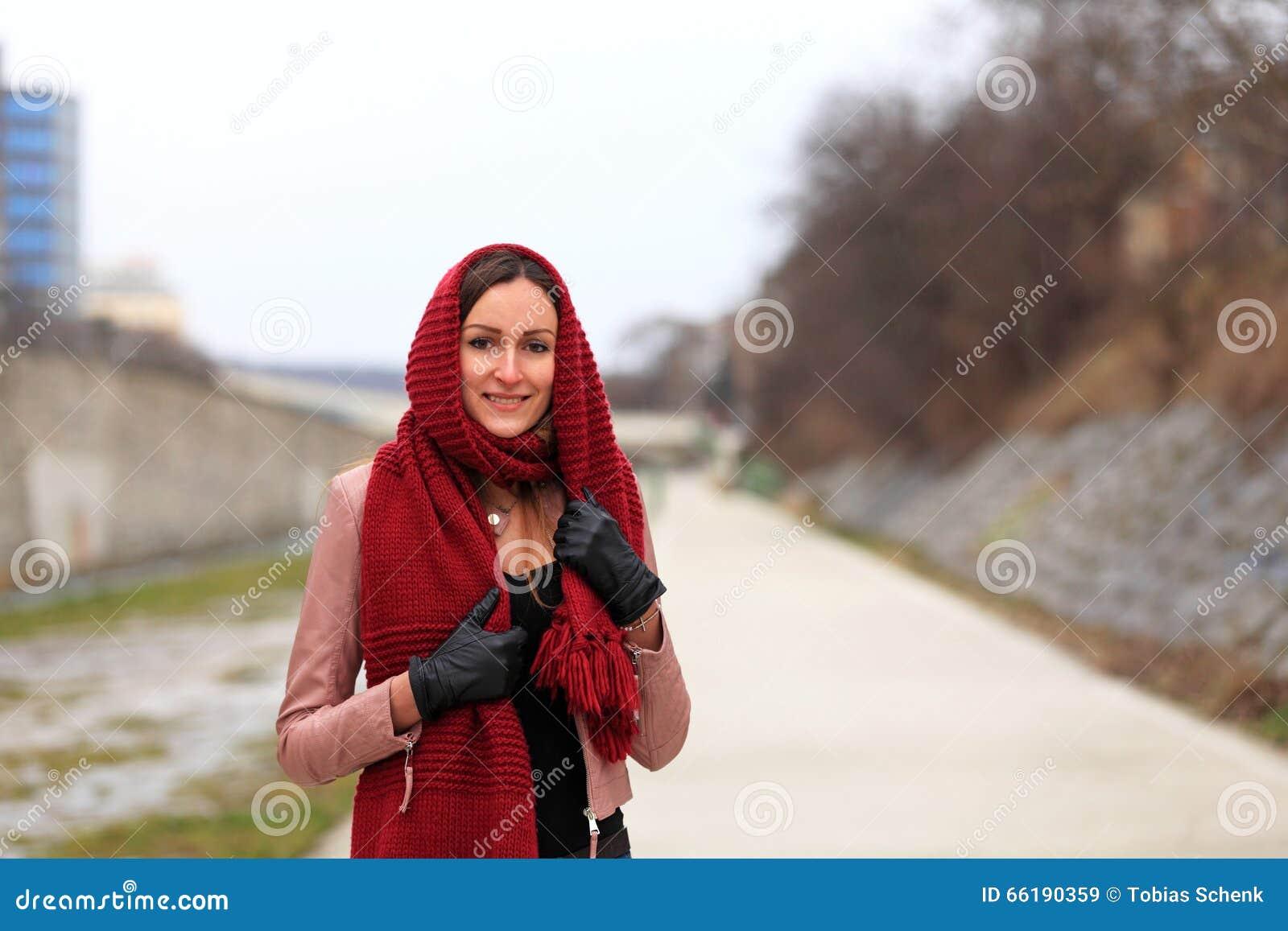Κορίτσι Brunette που φορά το σακάκι δέρματος με τα μαύρα γάντια και ένα κόκκινο μαντίλι