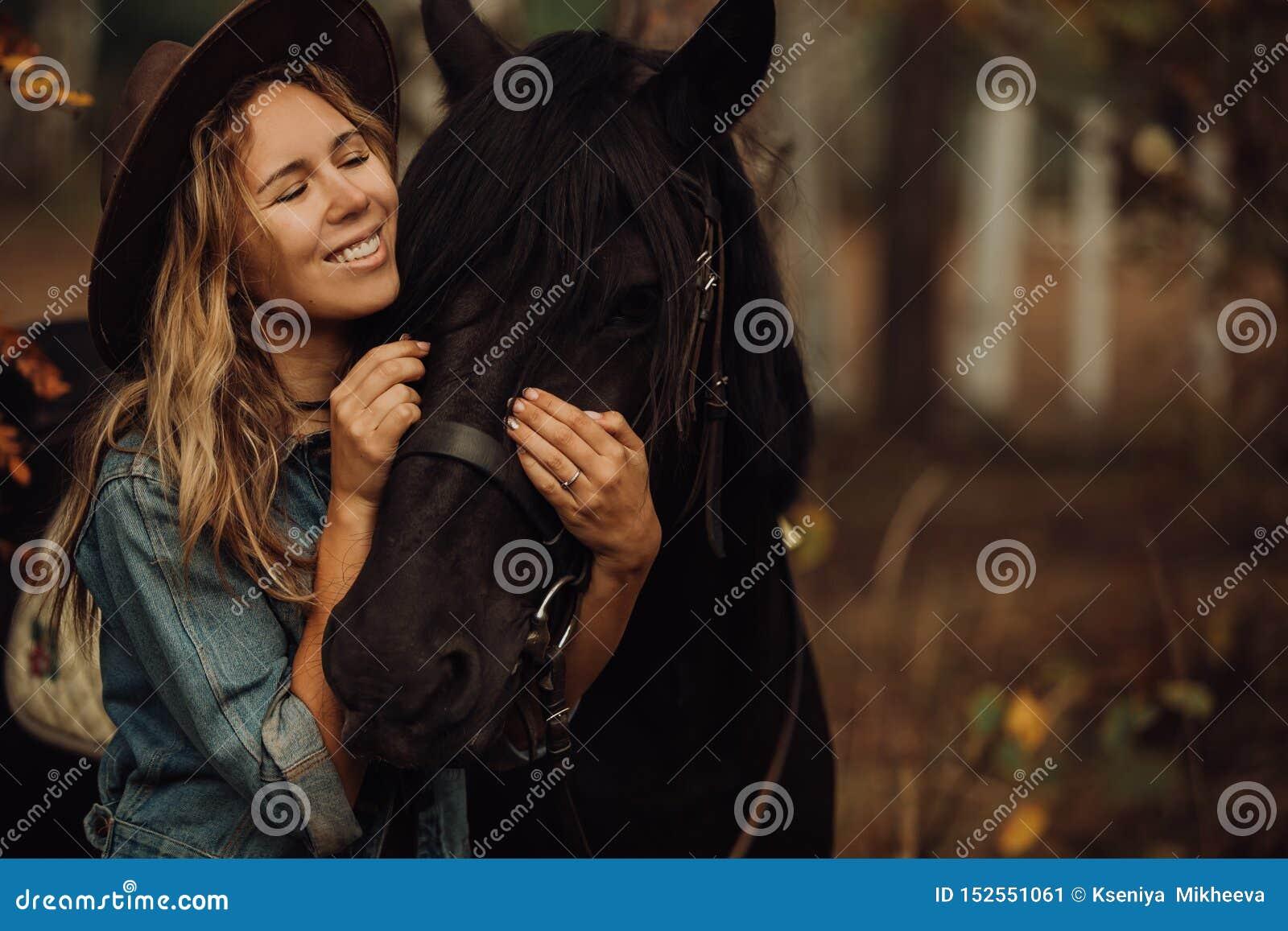Κορίτσι Hipster με ένα άλογο στο χαμόγελο ξύλων