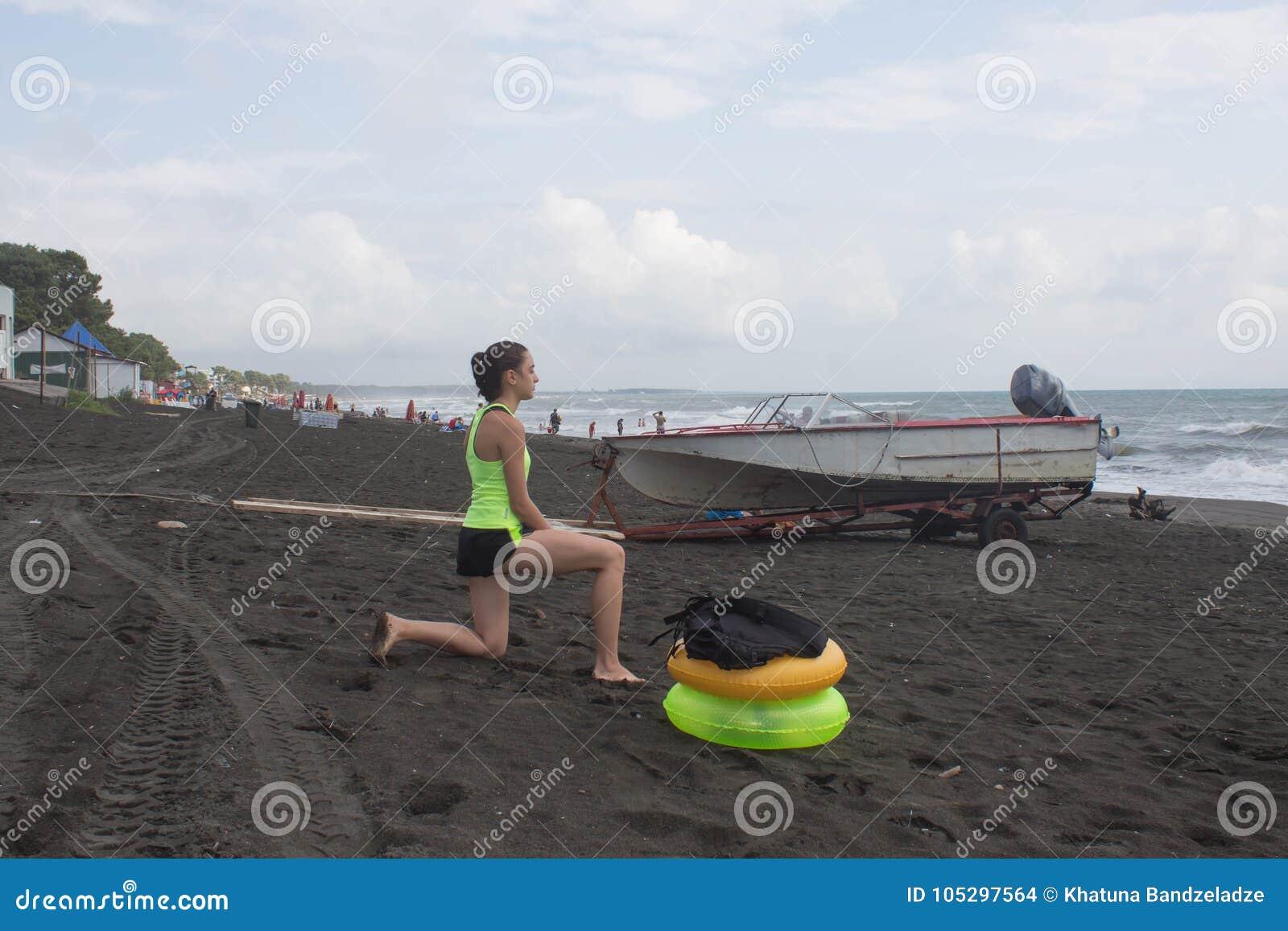 Κορίτσι, powerboat και κίτρινο, πράσινο επιπλέον δαχτυλίδι στην παραλία, συννεφιασμένος, σύννεφα, κύματα