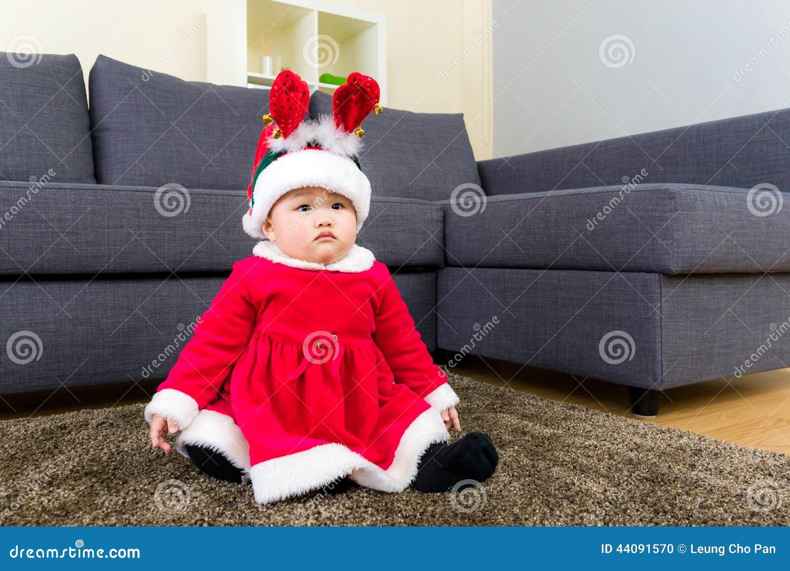 Κοριτσάκι με τη σάλτσα και τη διάταξη θέσεων Χριστουγέννων στον τάπητα