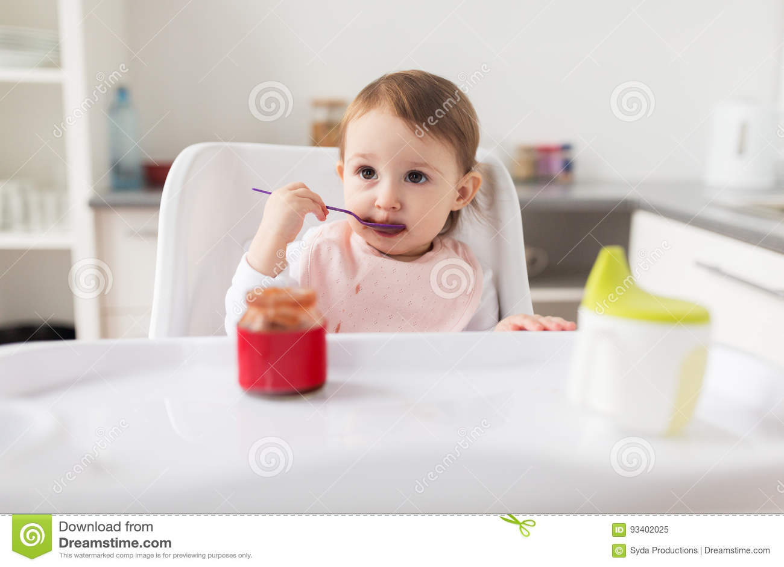Κοριτσάκι με το κουτάλι που τρώει τον πουρέ από το βάζο στο σπίτι