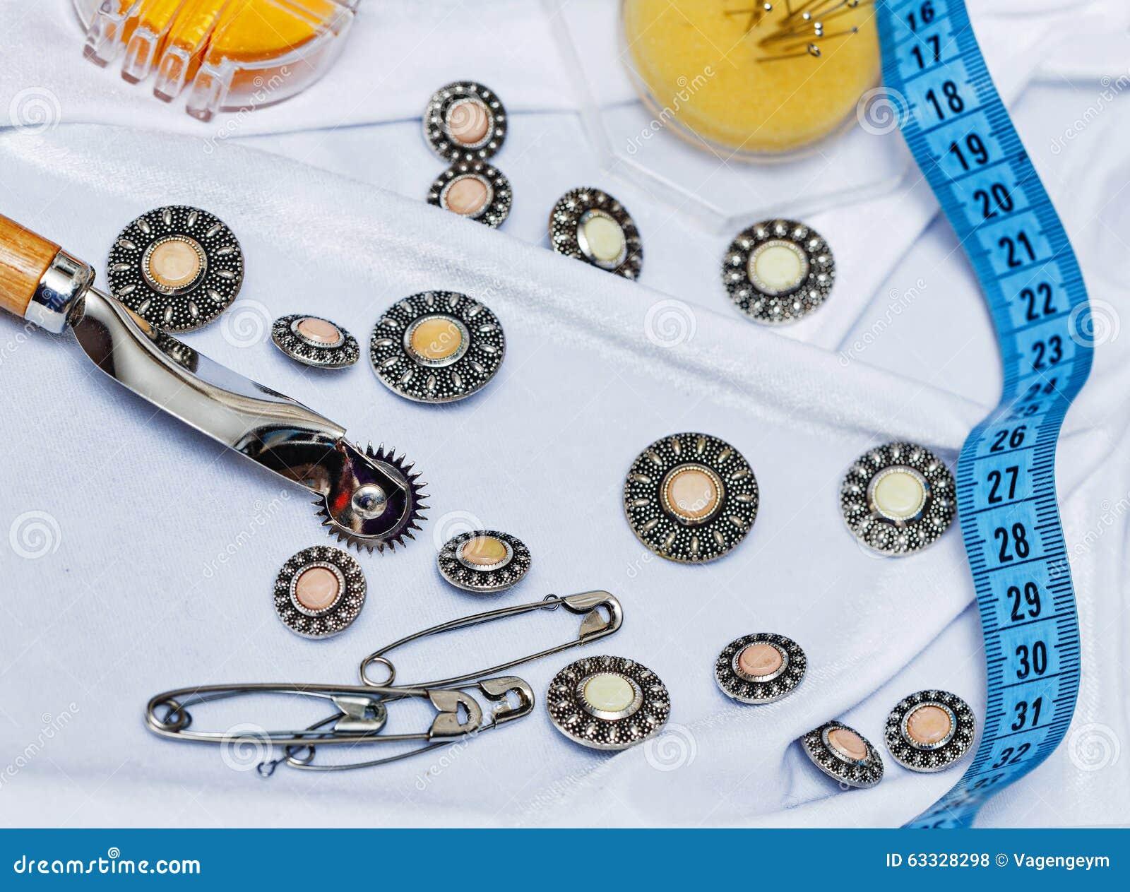 5f8050cb1cd4 Κουμπιά, καρφίτσες, που μετρούν την ταινία και μια βελόνα που βρίσκεται στο  ύφασμα μεταξιού Η έννοια της ραπτικής Σχέδιο μόδας Σπίτια μόδας Στοιχεία  για το ...
