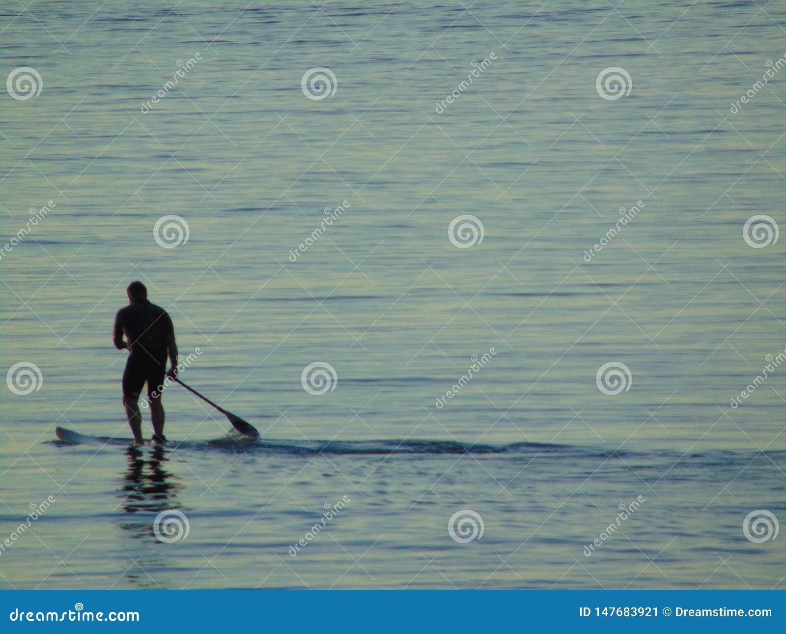 Κουπί άσκησης ατόμων που κάνει σερφ στη θάλασσα