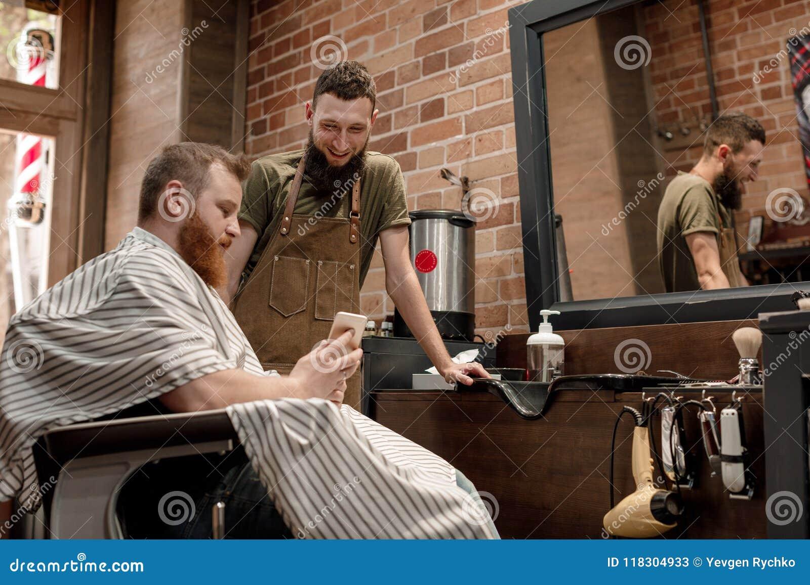 Κουρέας και γενειοφόρο άτομο στο κατάστημα κουρέων