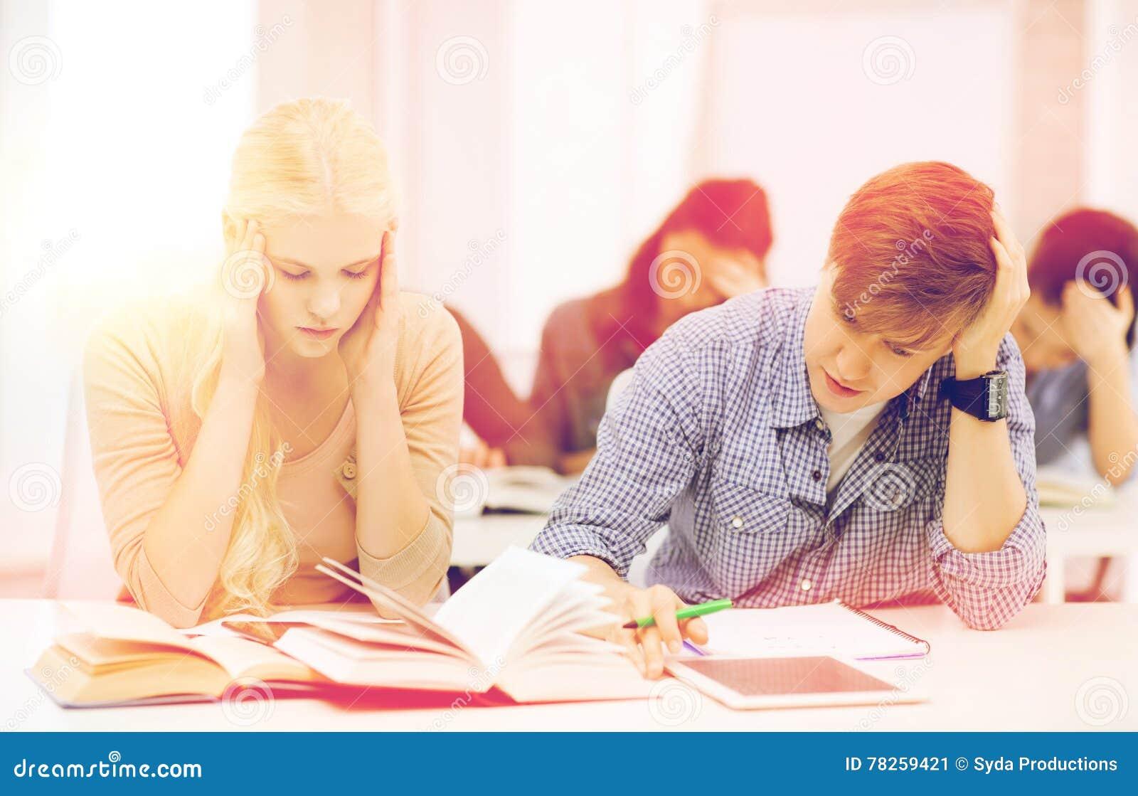 Κουρασμένοι σπουδαστές με το PC ταμπλετών, τα σημειωματάρια και τα βιβλία