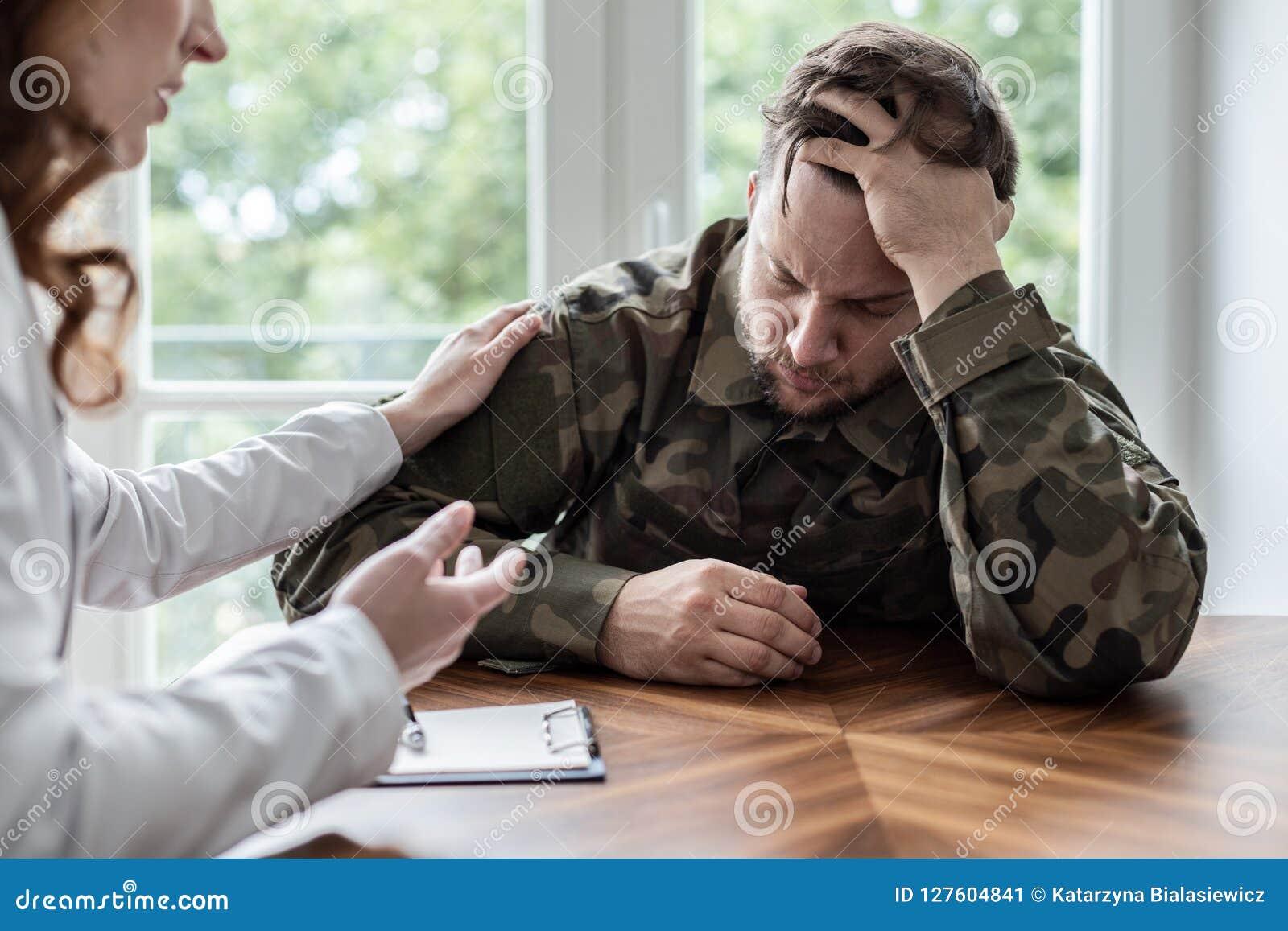 Κουρασμένος και λυπημένος στρατιώτης με το πολεμικό σύνδρομο κατά τη διάρκεια της θεραπείας με τον ψυχοθεραπευτή