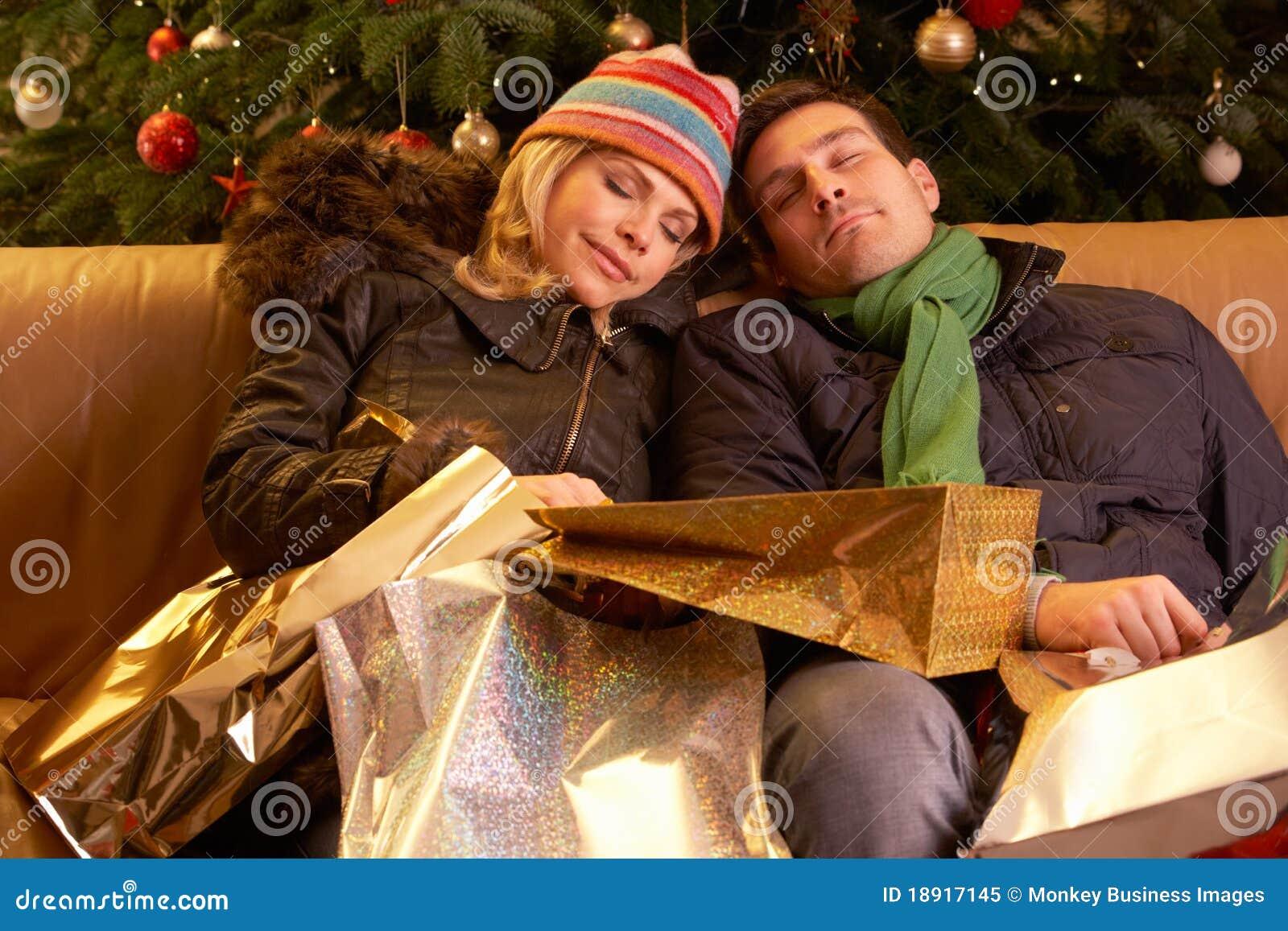 Κουρασμένο ζεύγος που επιστρέφει μετά από τις αγορές Χριστουγέννων