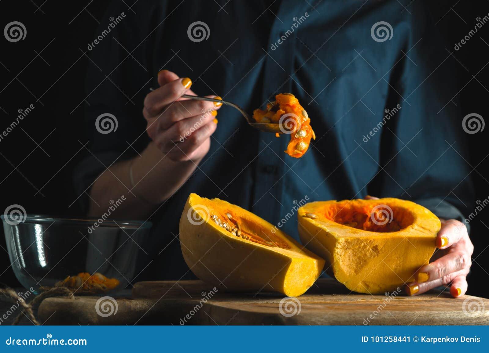 Κουτάλι με τους σπόρους σε ένα χέρι, μισά κολοκύθας σε έναν πίνακα σε ένα μπλε υπόβαθρο