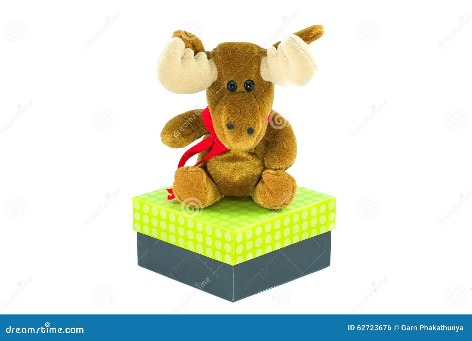 Κούκλα ταράνδων για τα Χριστούγεννα πέρα από ένα κιβώτιο δώρων που απομονώνεται στο άσπρο BA